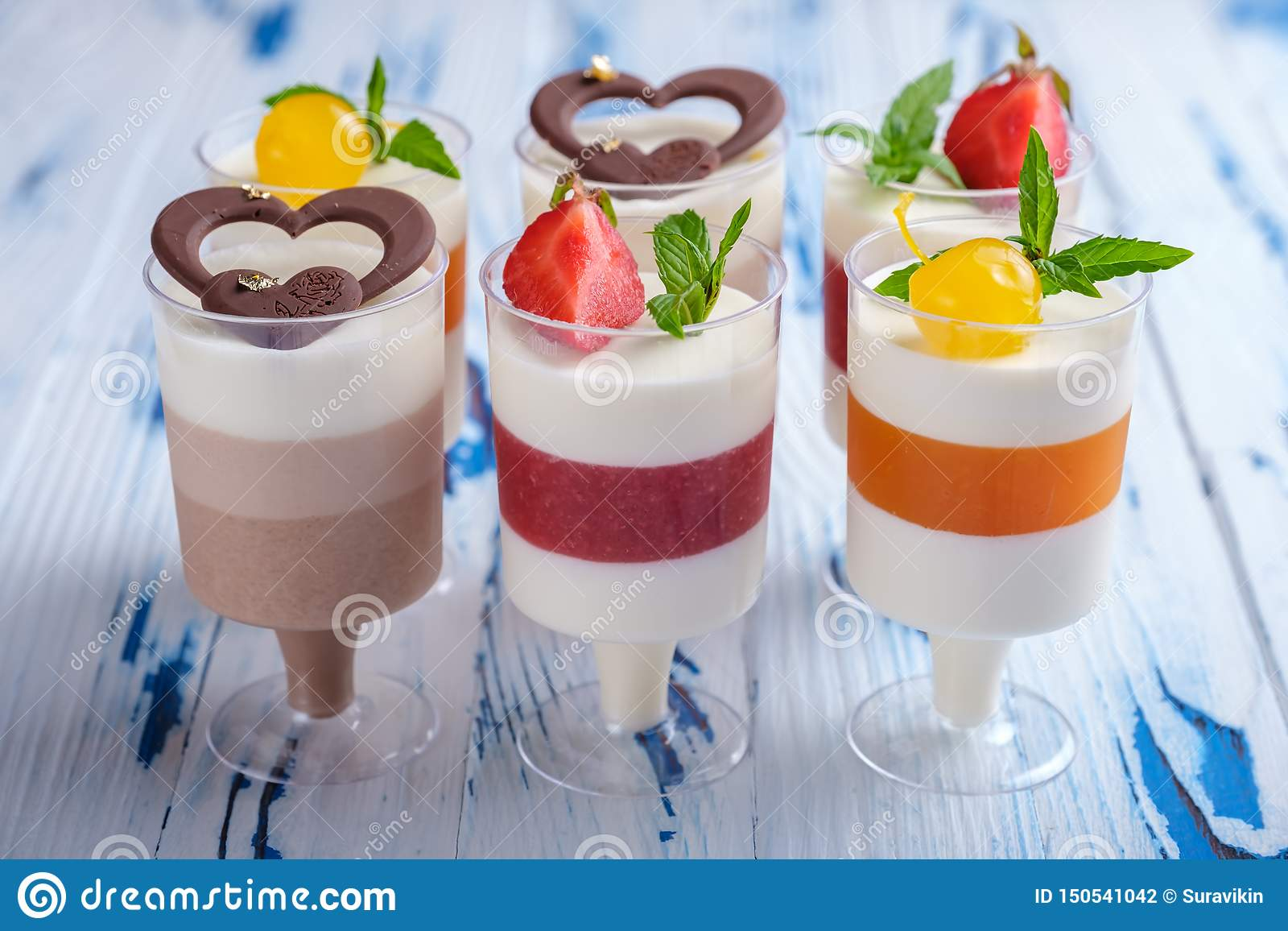 Six mousse desserts in wineglasses, decorated chocolate, strawberry, mint and cocktail cherries on aged wooden table