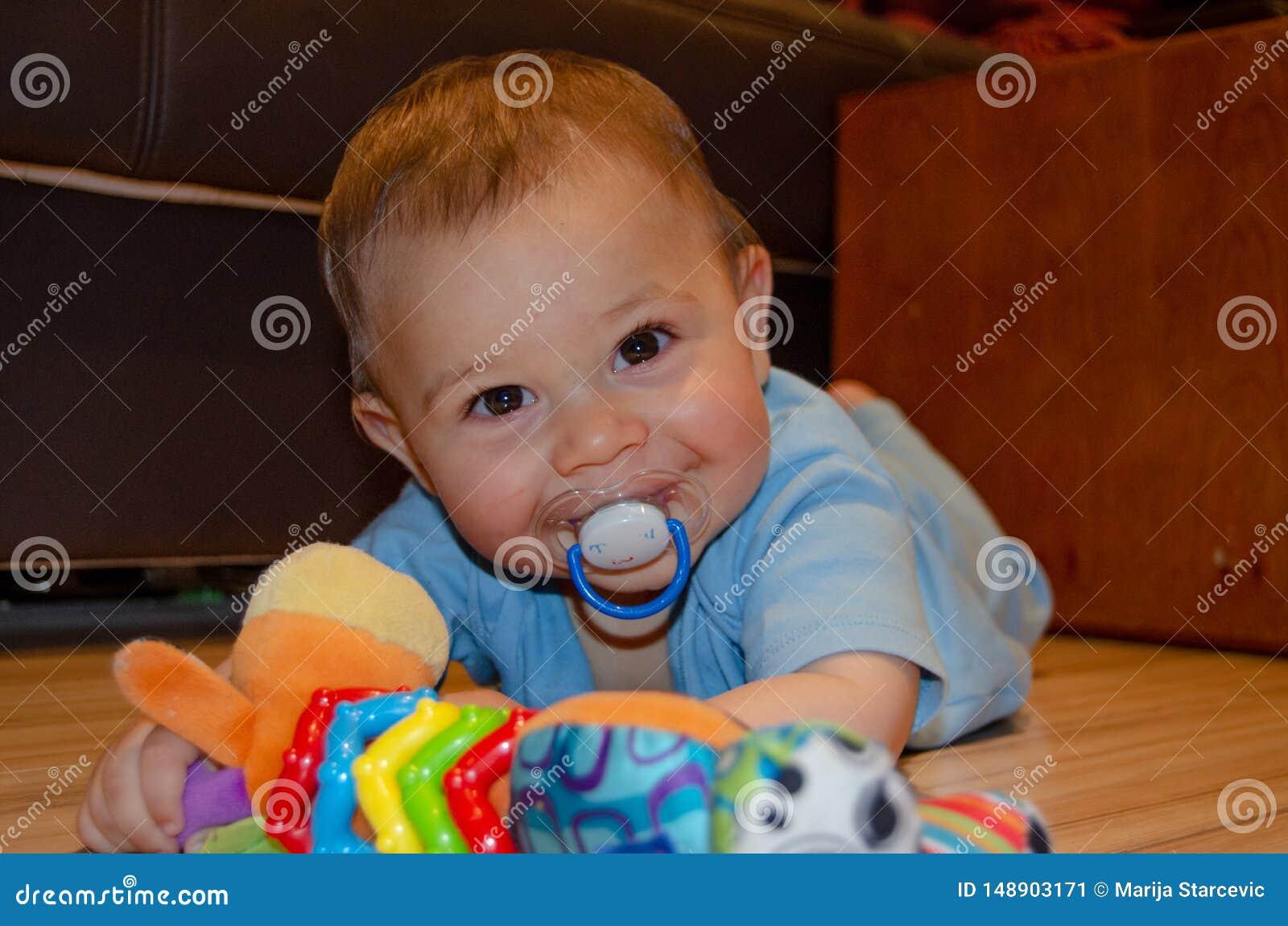 Six mois mignons de b?b? gar?on jouant sur Flor avec le jouet de dentition, d?veloppement pr?coce et faisant ses dents le concept