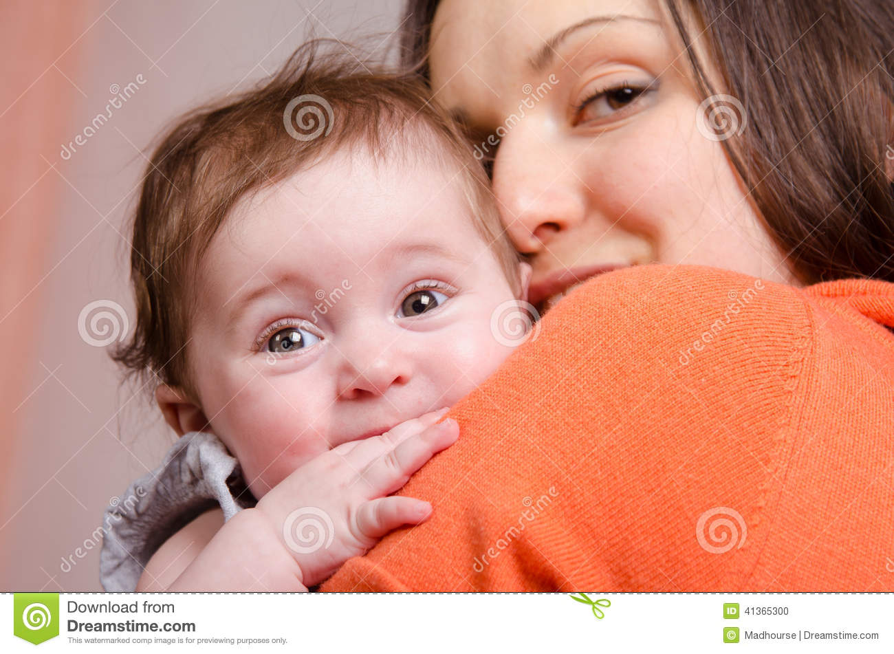 Six-month baby girl on hands happy mom