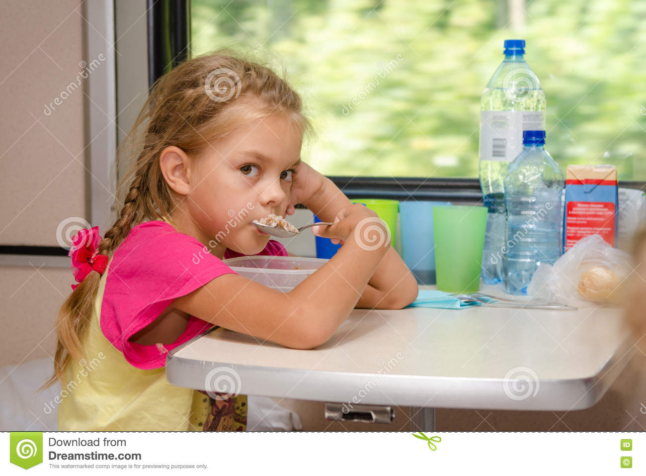 A six-year girl in a train sitting at table on the lower place in the second-class compartment of the car and eats porridge sp