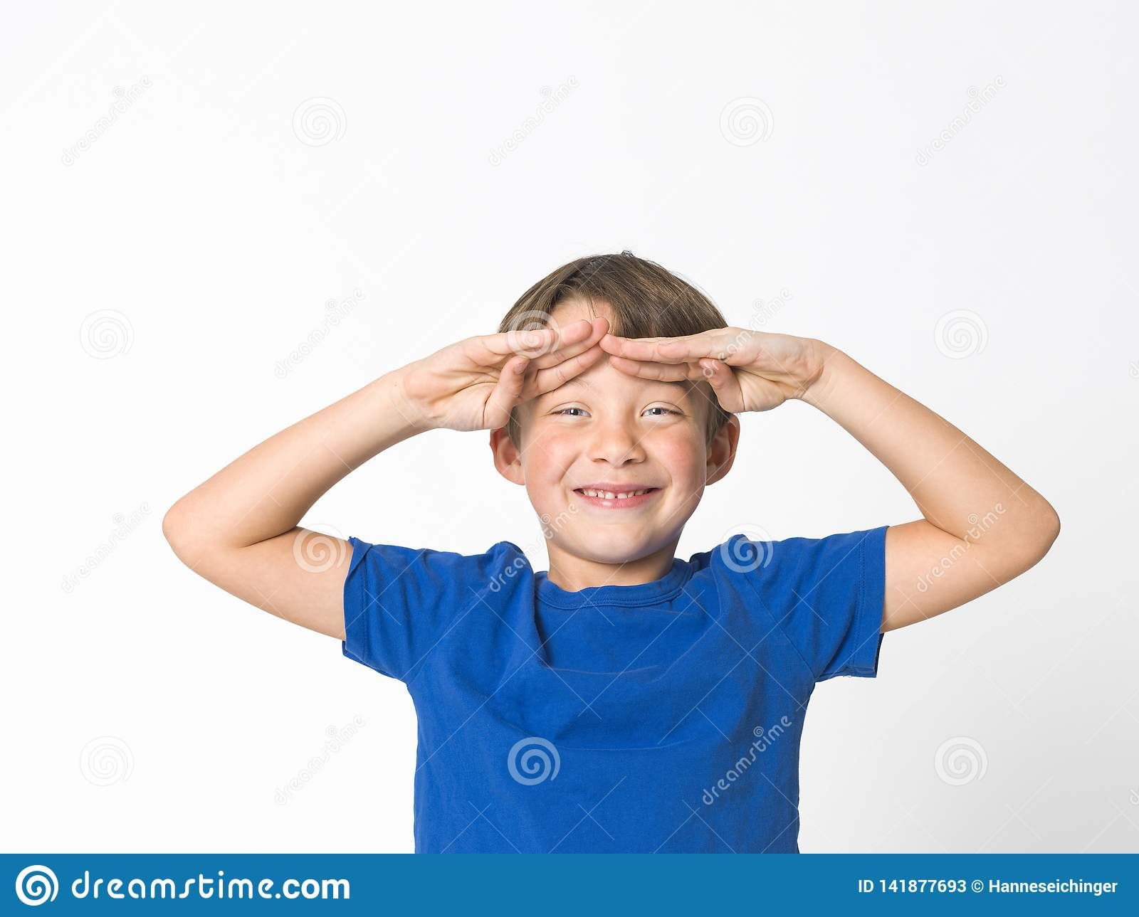 Cool and cute six year old boy in red trousers and blue shirt is posing in front of white background