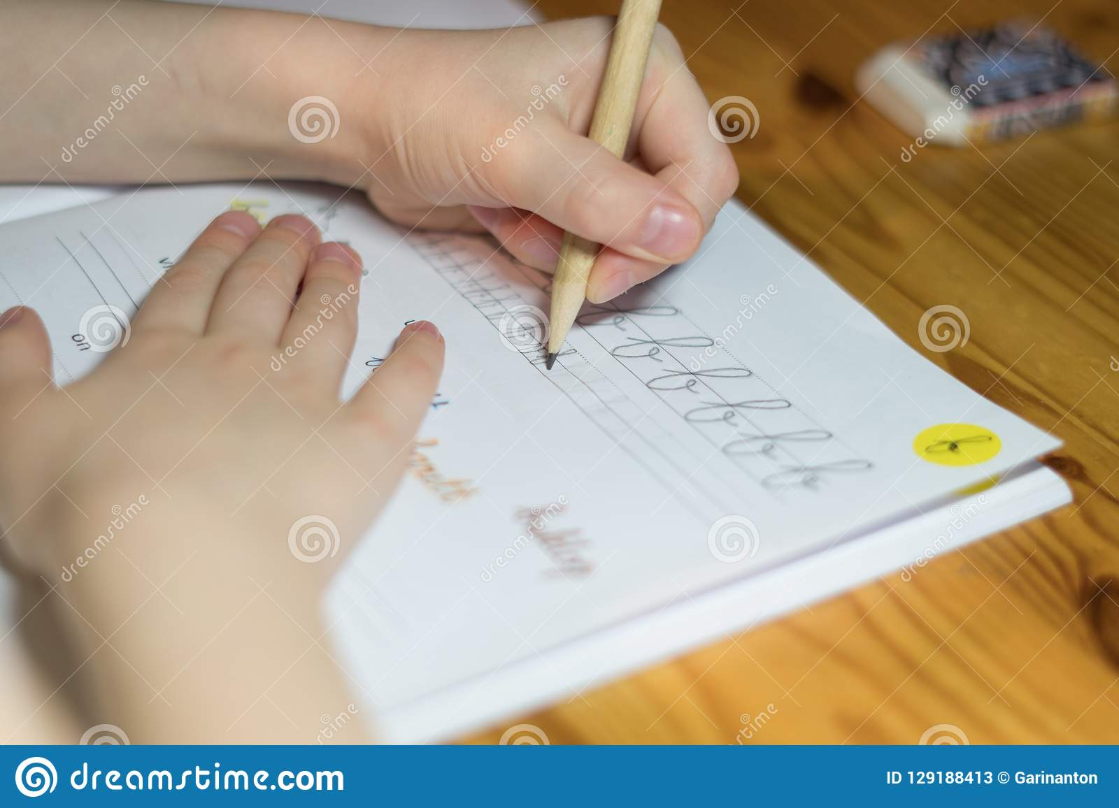 A six year old girl is practicing writing in a notebook.