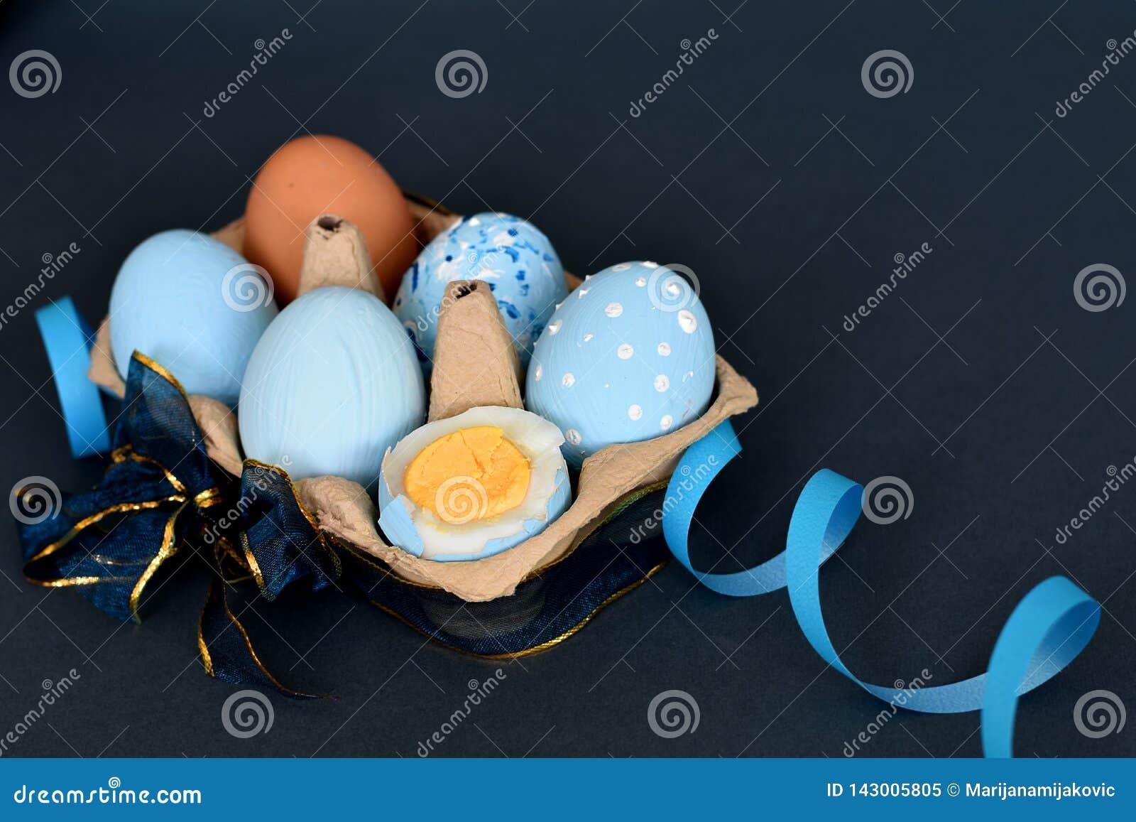 Sixpack av ljust - blåa kulöra påskägg som dekoreras med band