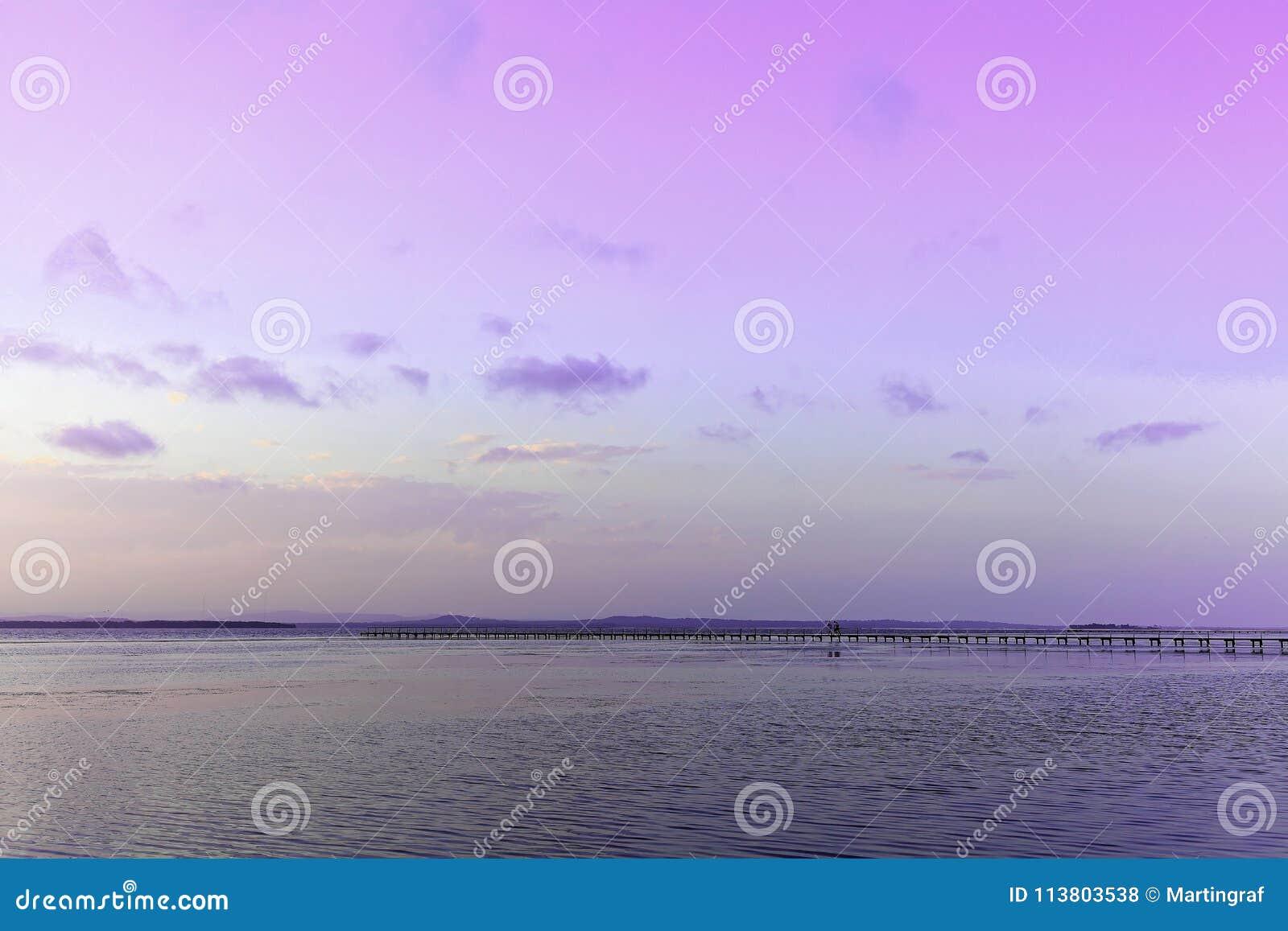 Sjölandskap med bryggan vid violett himmel på solnedgången