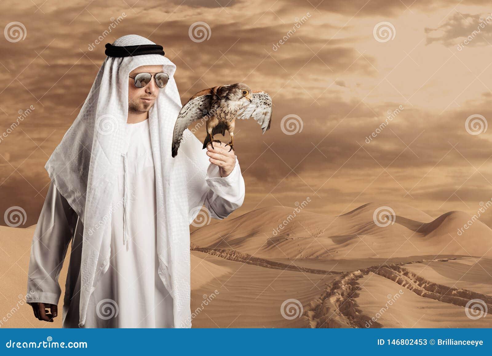 Sjeik die met zonnebril een valk voor woestijnheuvels en voetstappen houden