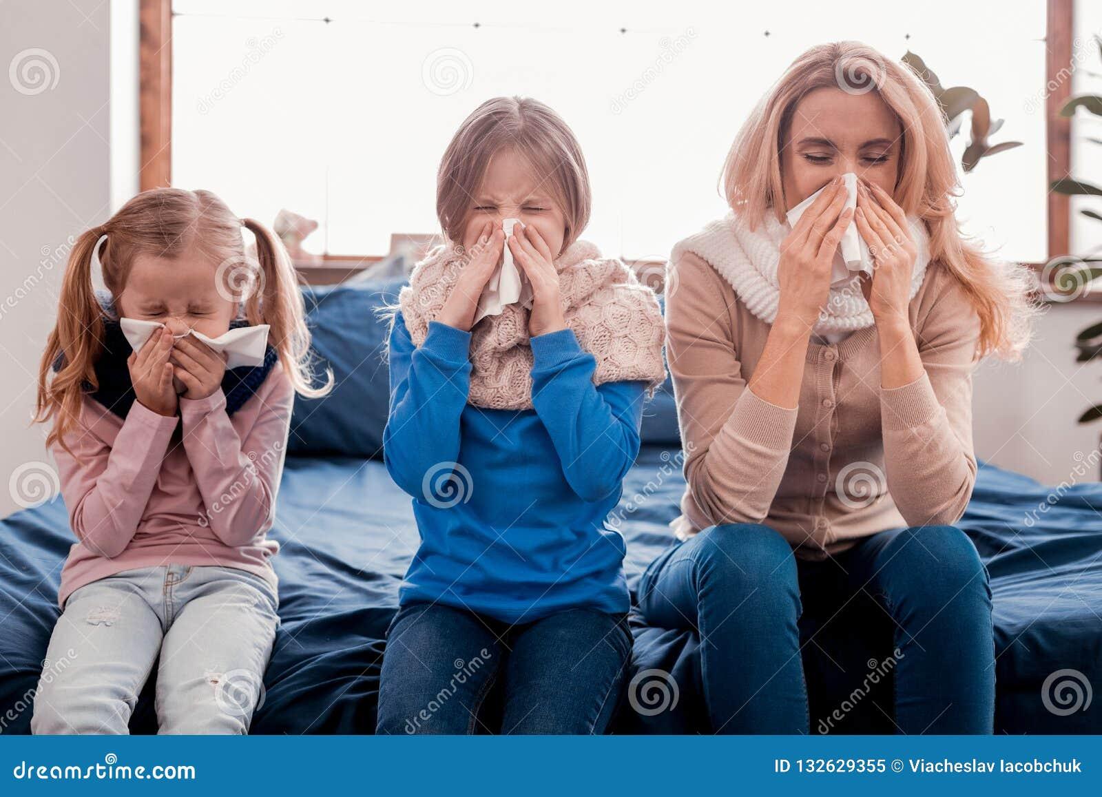 Sjuk familj som sitter på sängen