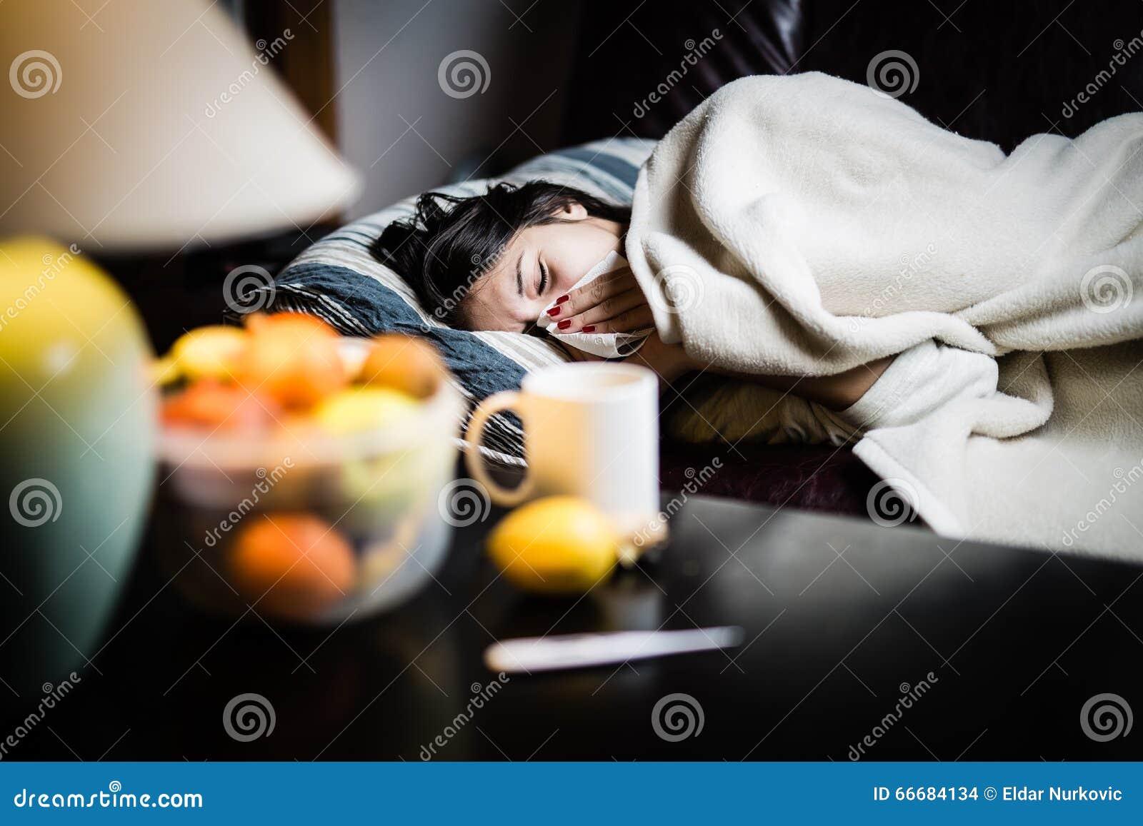 Sjuk kvinna i säng som kallar i sjukt, fridag från arbete Termometer som kontrollerar temperaturen för feber