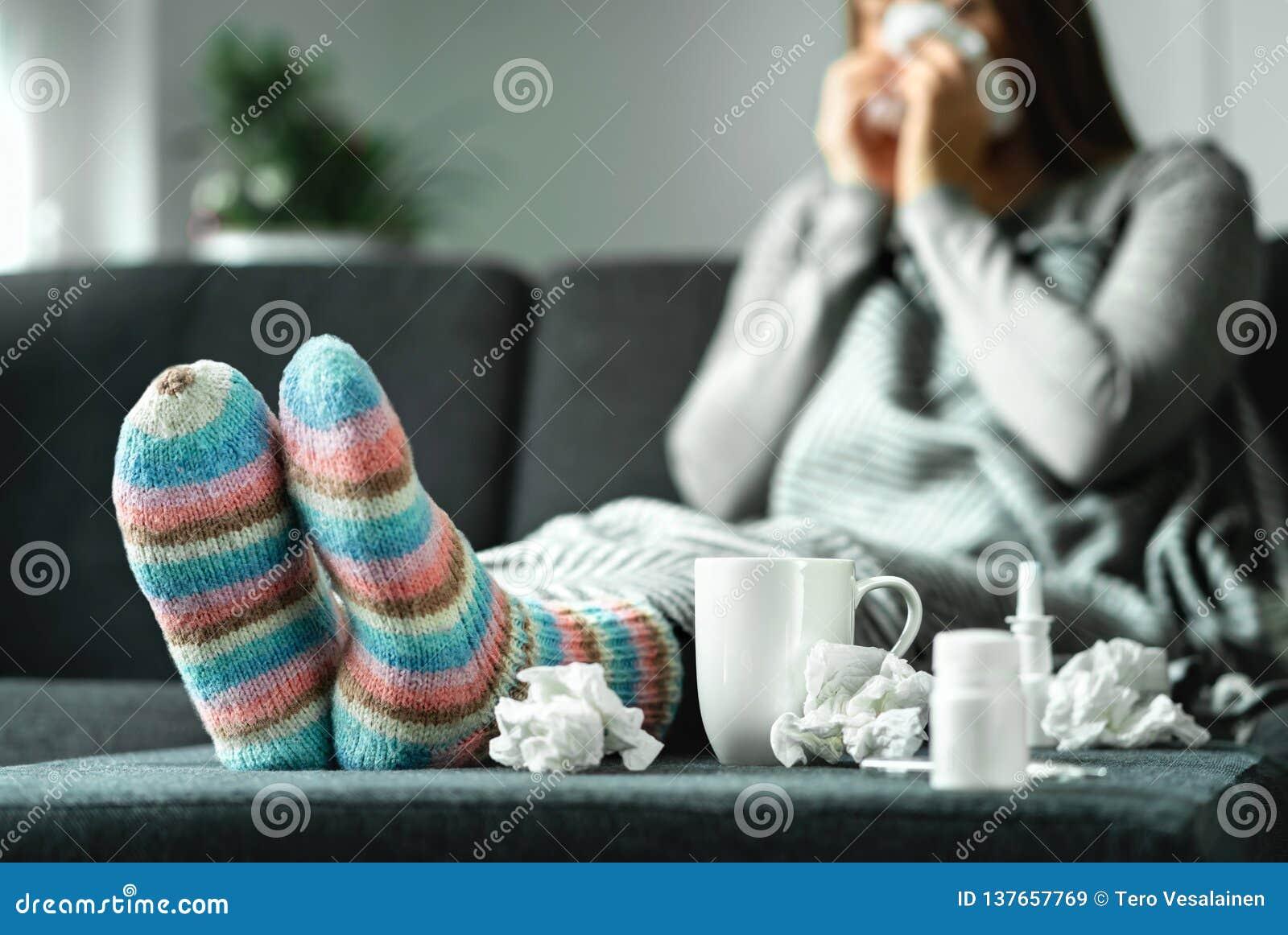 Sjuk kvinna med influensa, förkylning, feber och hosta som hemma sitter på soffan Dåligt blåsa näsa för person och nysa med silke