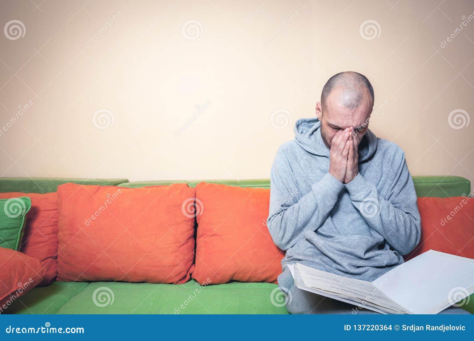 Sjuk man för ung eller mellersta ålder i den tillfälliga kläderna som läser läkareresultat på legitimationshandlingar från hans d