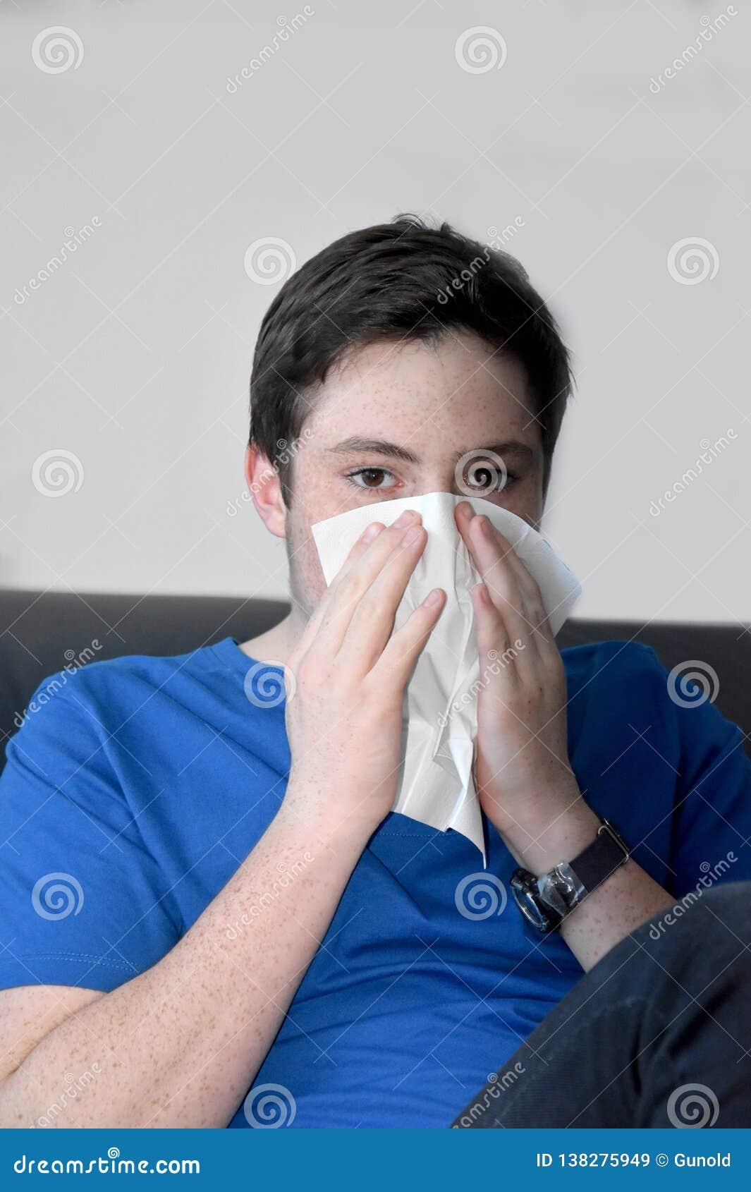 Sjuk tonårs- pojke som blåser hans näsa