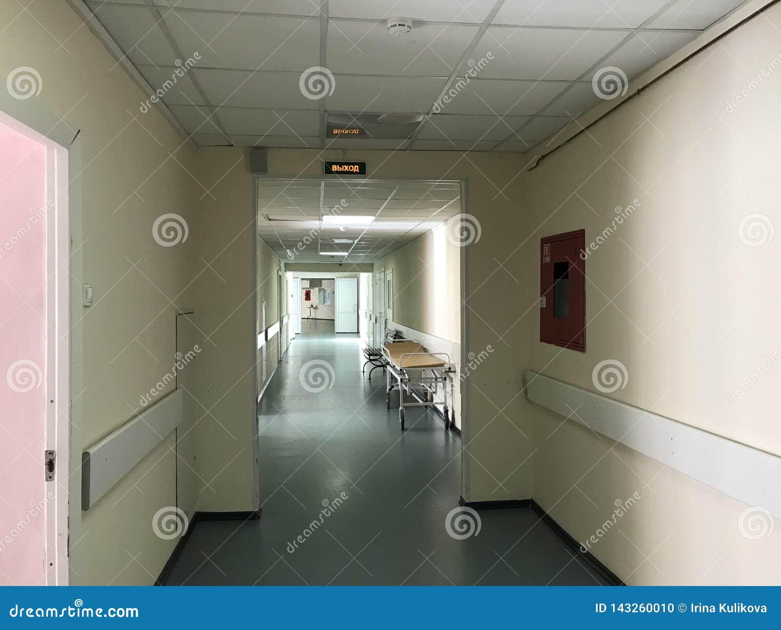 Sjukhusinre: sikt av en lång korridor med ljusa väggar i sjukhuset