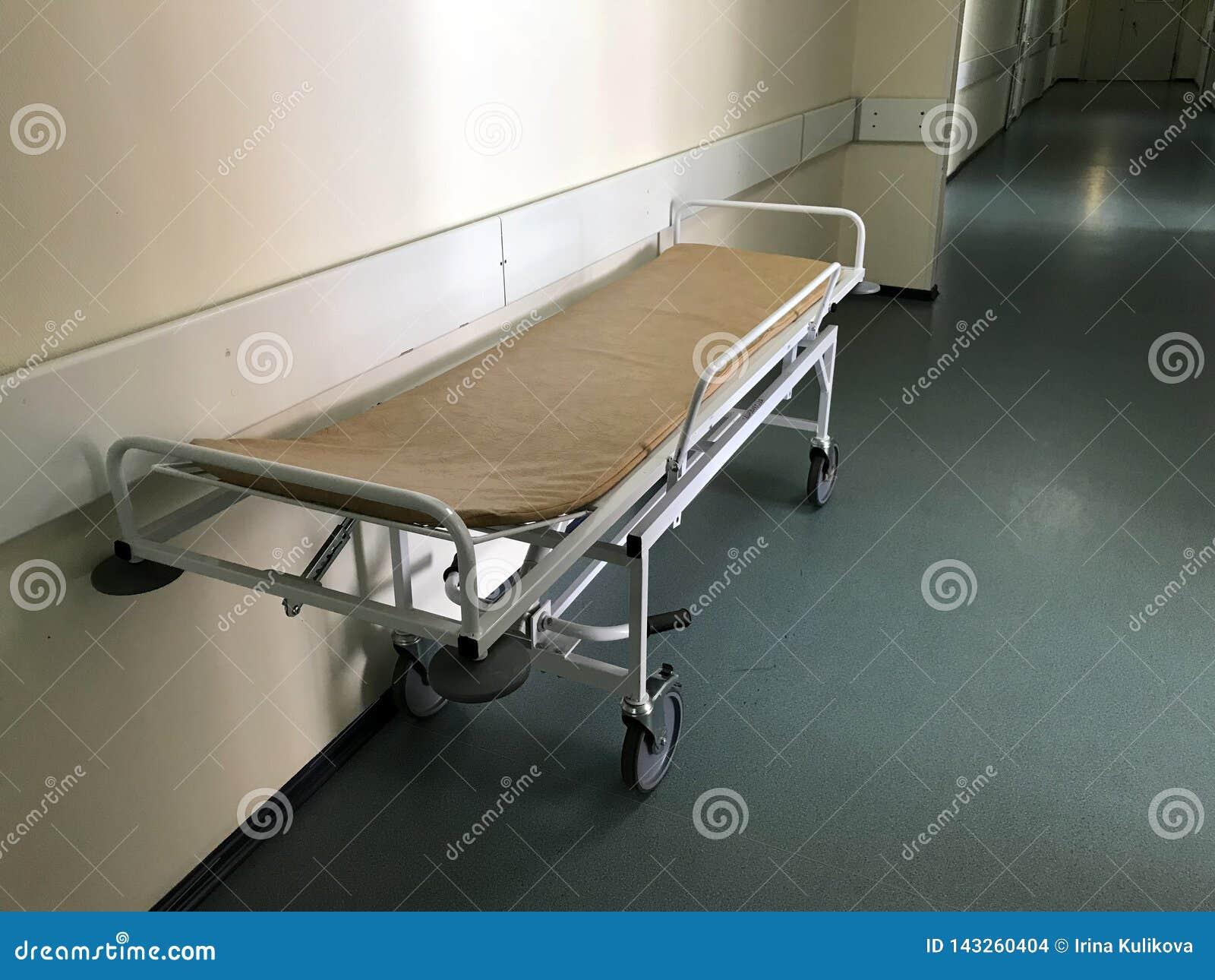 Sjukhusinre: sikt av en lång korridor och en gurney i sjukhuset