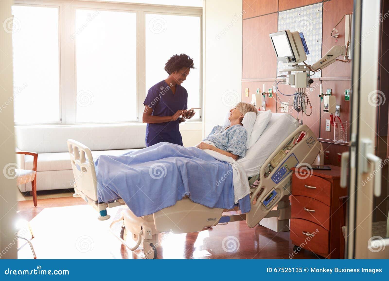 Sjukhussjuksköterskan With Digital Tablet talar till den höga patienten