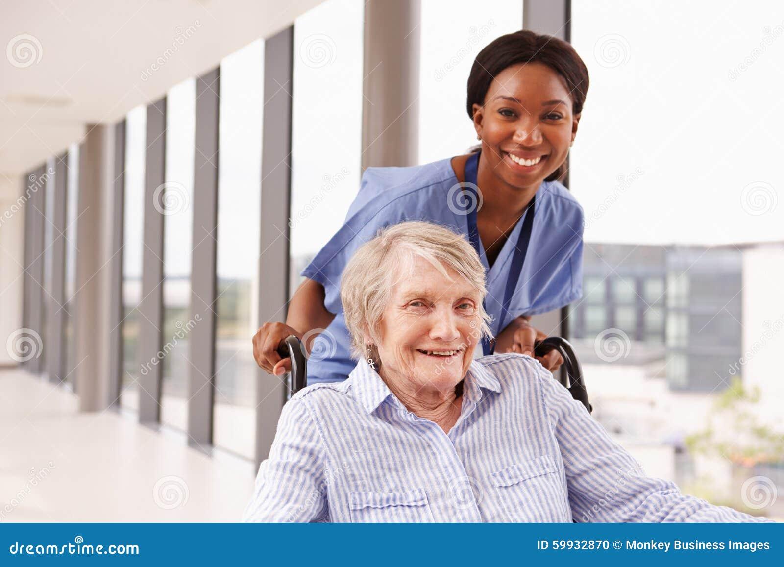 Sjuksköterska Pushing Senior Patient i rullstol längs korridoren