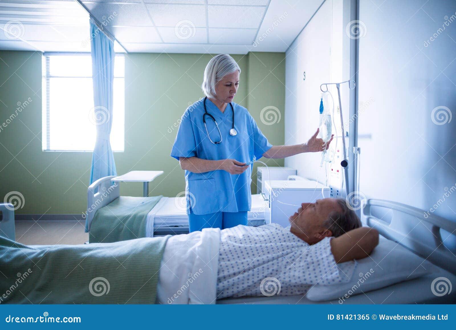 Sjuksköterska som justerar manlig iv-droppande för patient s