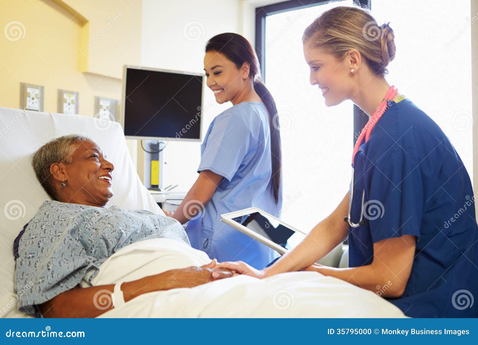 Sjuksköterskan With Digital Tablet talar till kvinnan i sjukhussäng