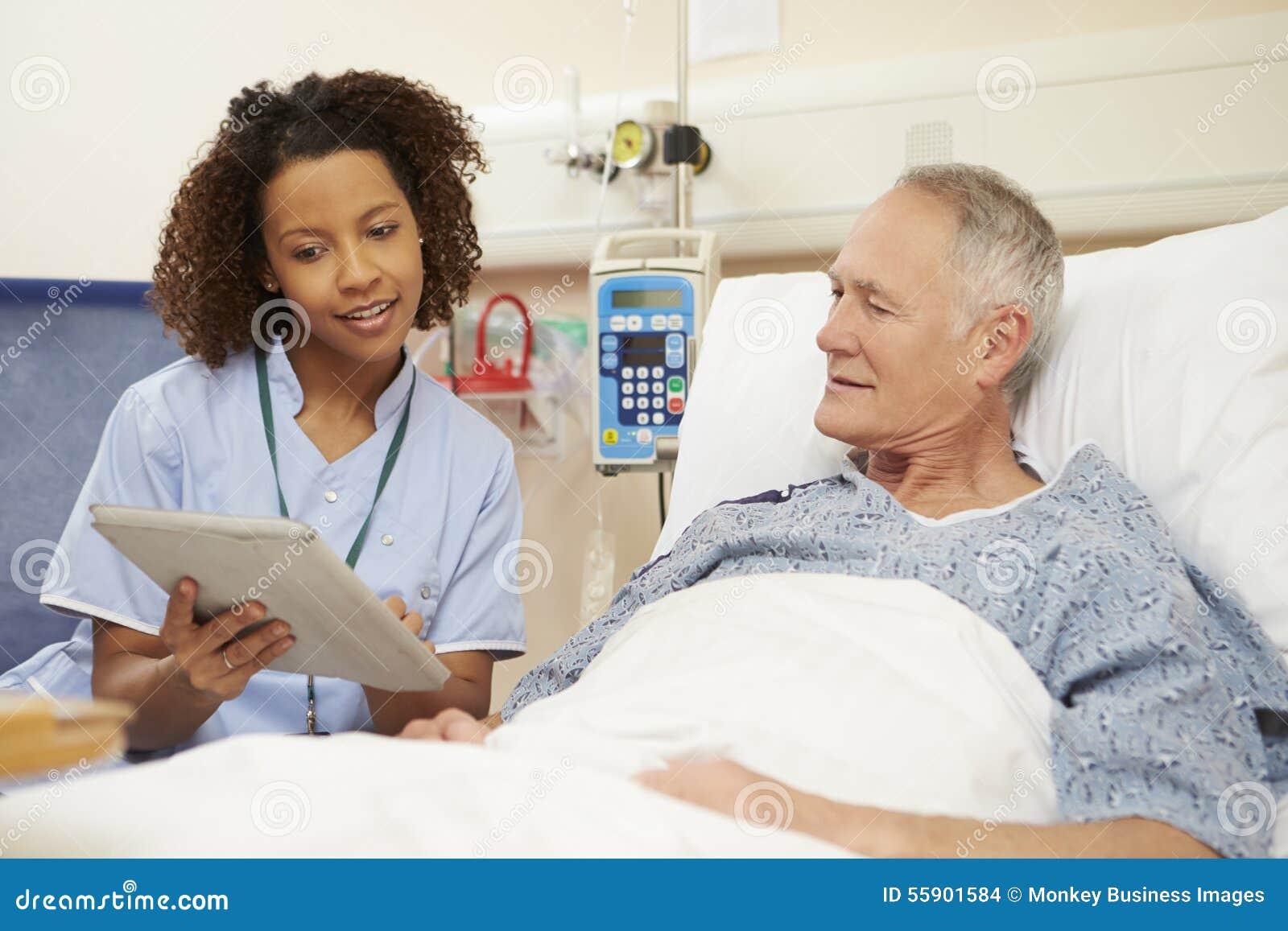 SjuksköterskaSitting By Male patients säng genom att använda den Digital minnestavlan