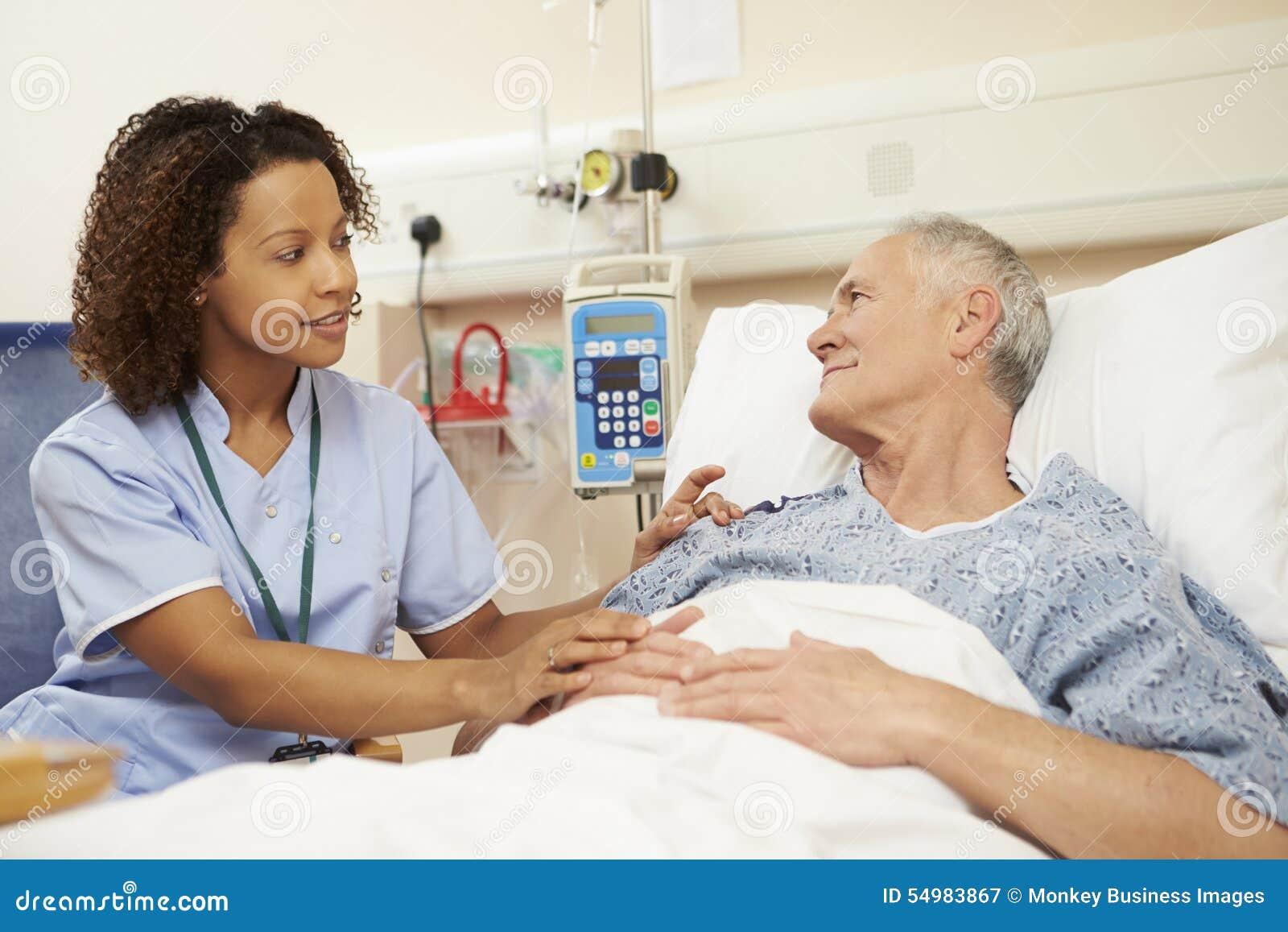 SjuksköterskaSitting By Male patients säng i sjukhus