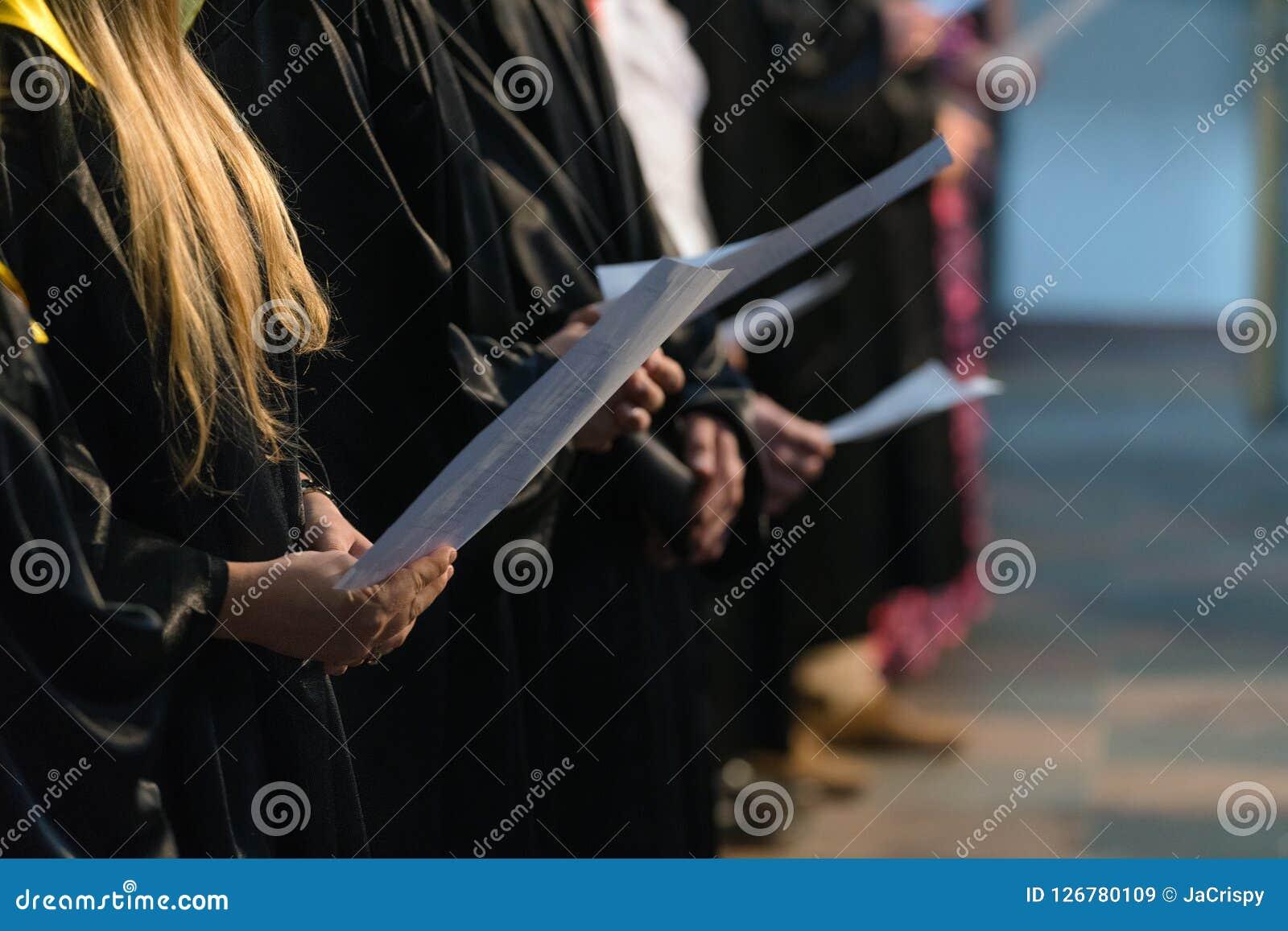 Sjunga i kör sångare som rymmer den musikaliska ställningen och sjunger på studentgradu