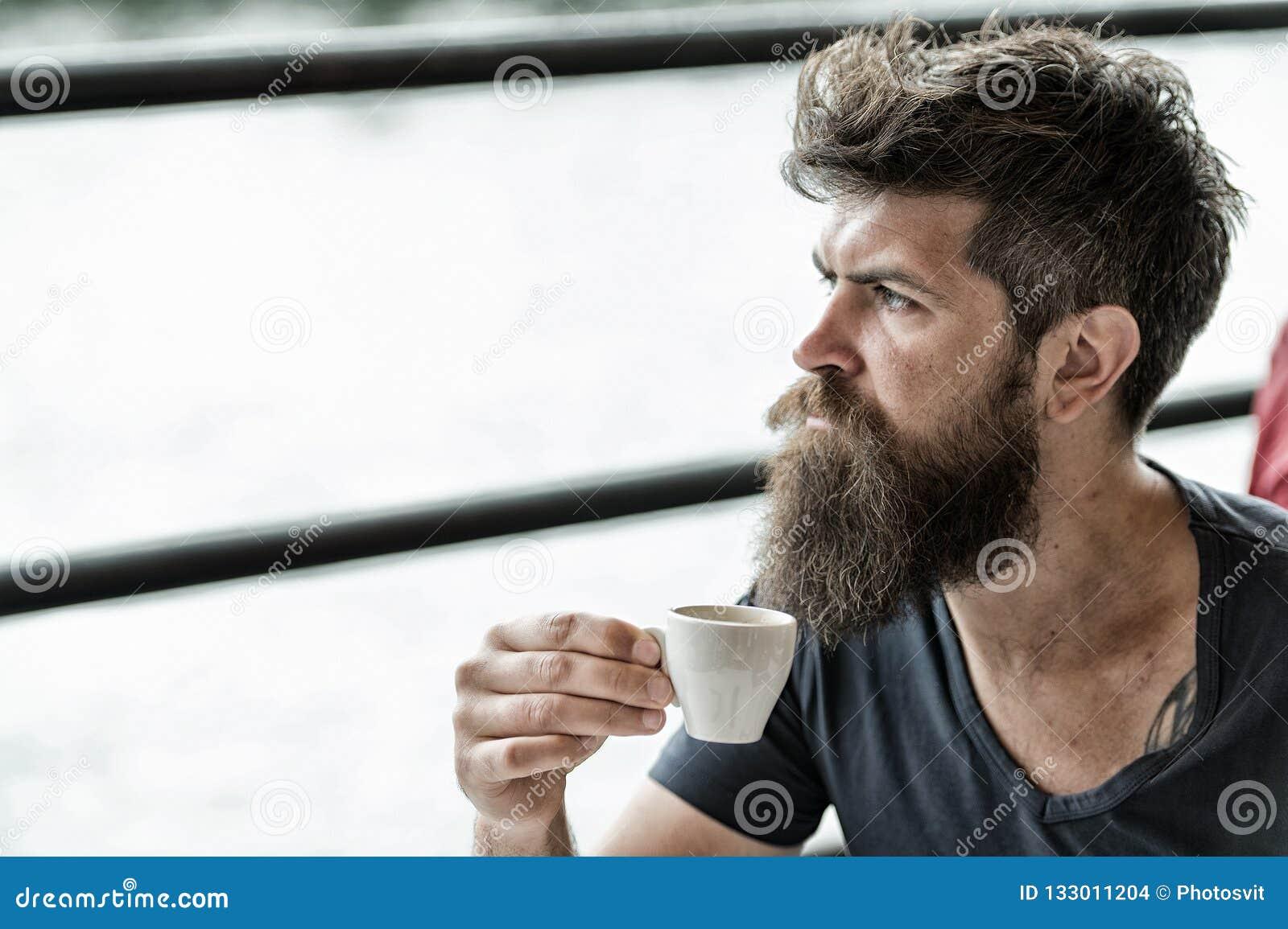 Skäggig grabb som kopplar av på kaféterrassen Grabb som kopplar av med espressokaffe ta för man för avbrottskaffebegrepp Hipster