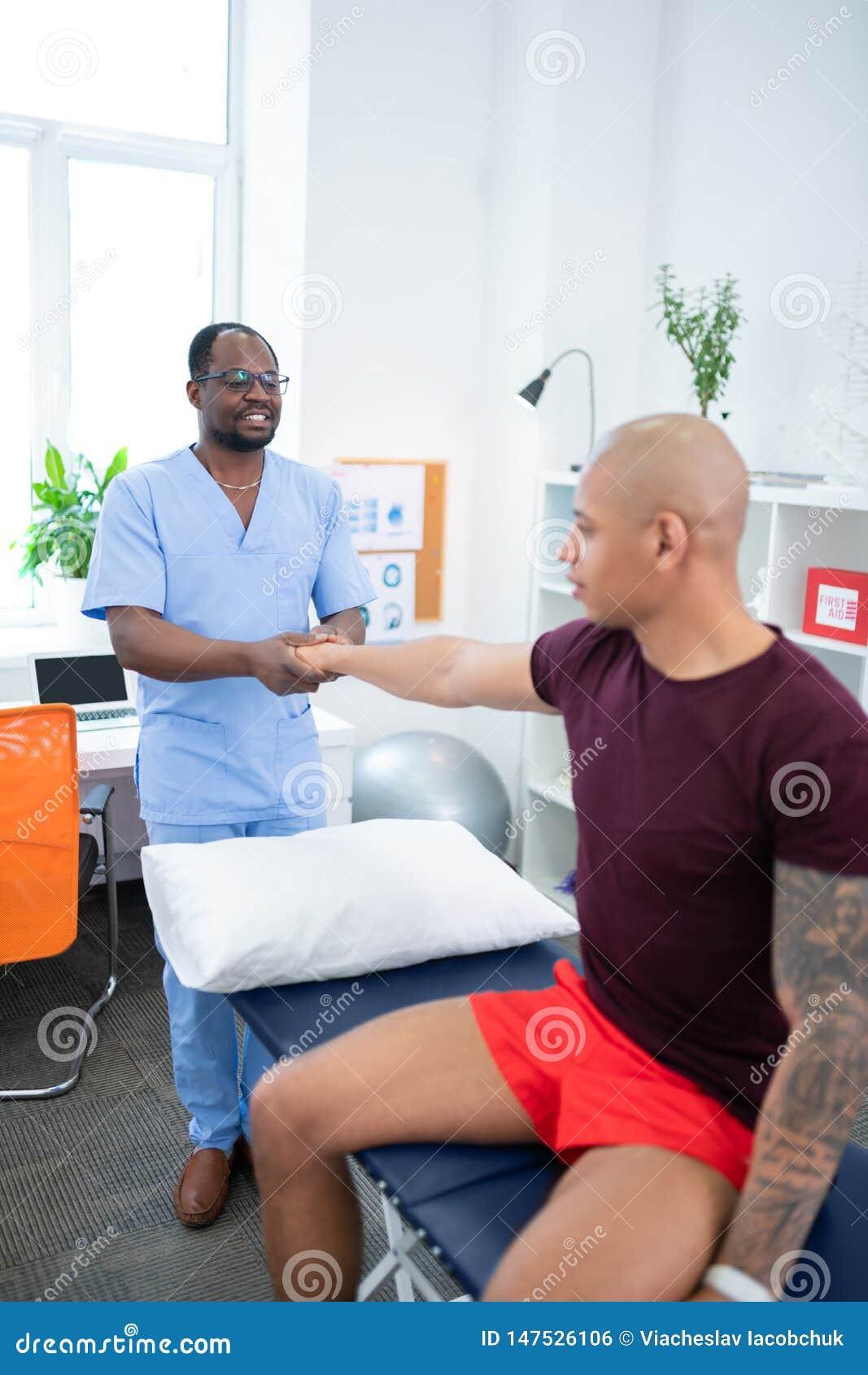 Skäggig mörkhyad fysisk terapeut som talar till hans besökare