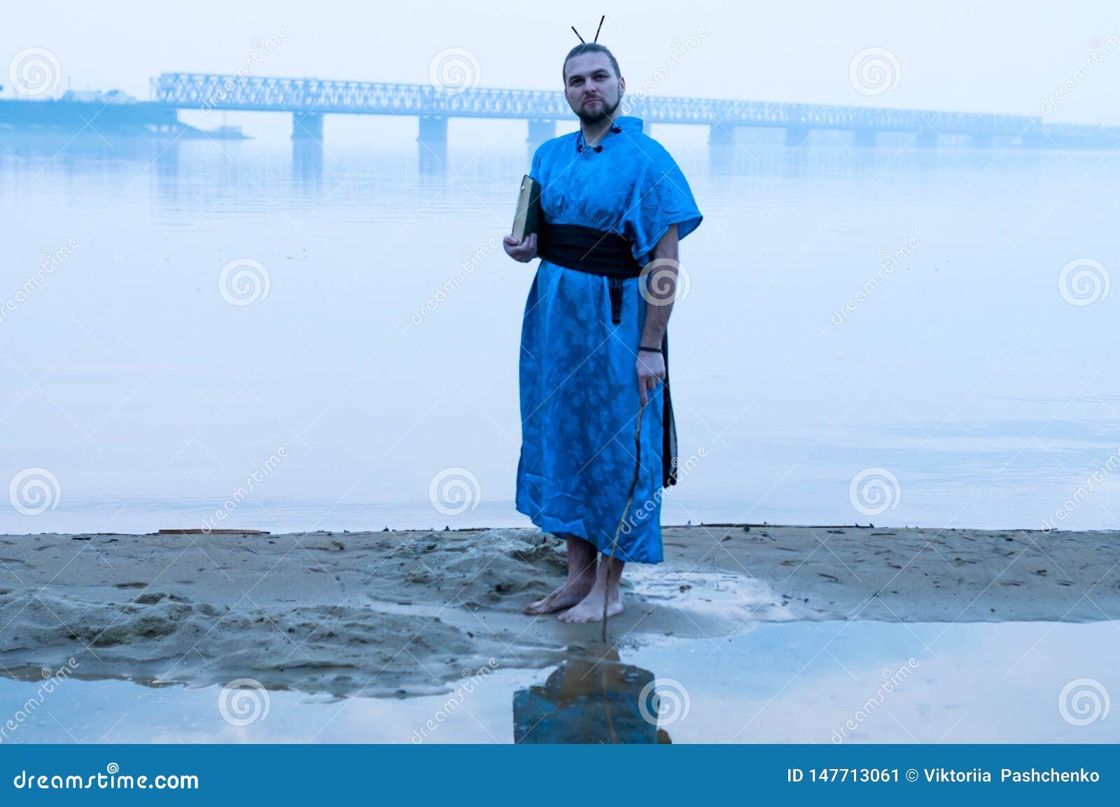 Skäggig man i blå kimonoinnehavbok på flodbanken i dimma och se kameran