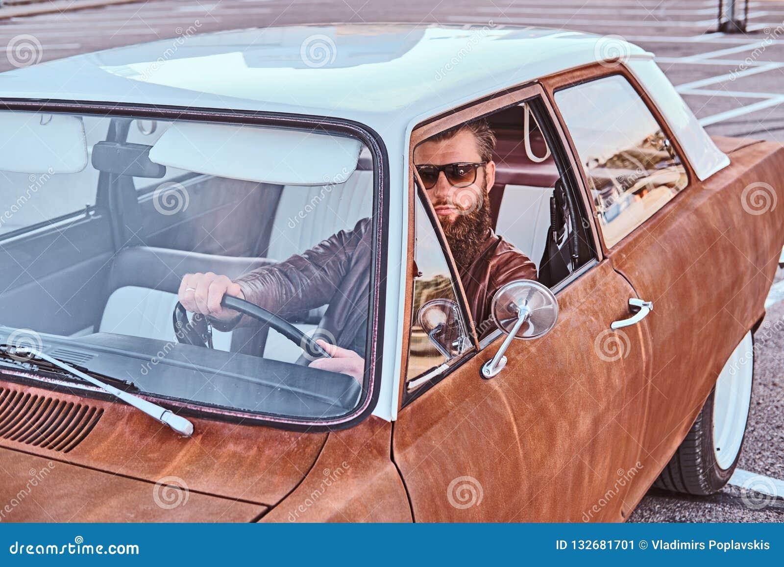 Skäggig man i för bruntläder för solglasögon som det iklädda omslaget kör en retro bil