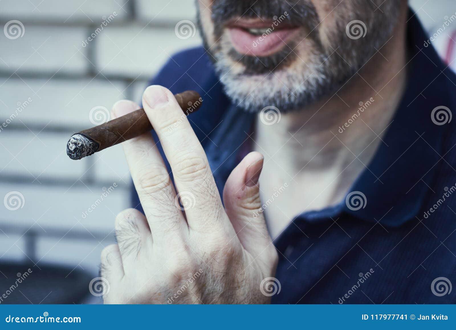 Skäggig succusful man som kyler och röker den dyrbara cigarren