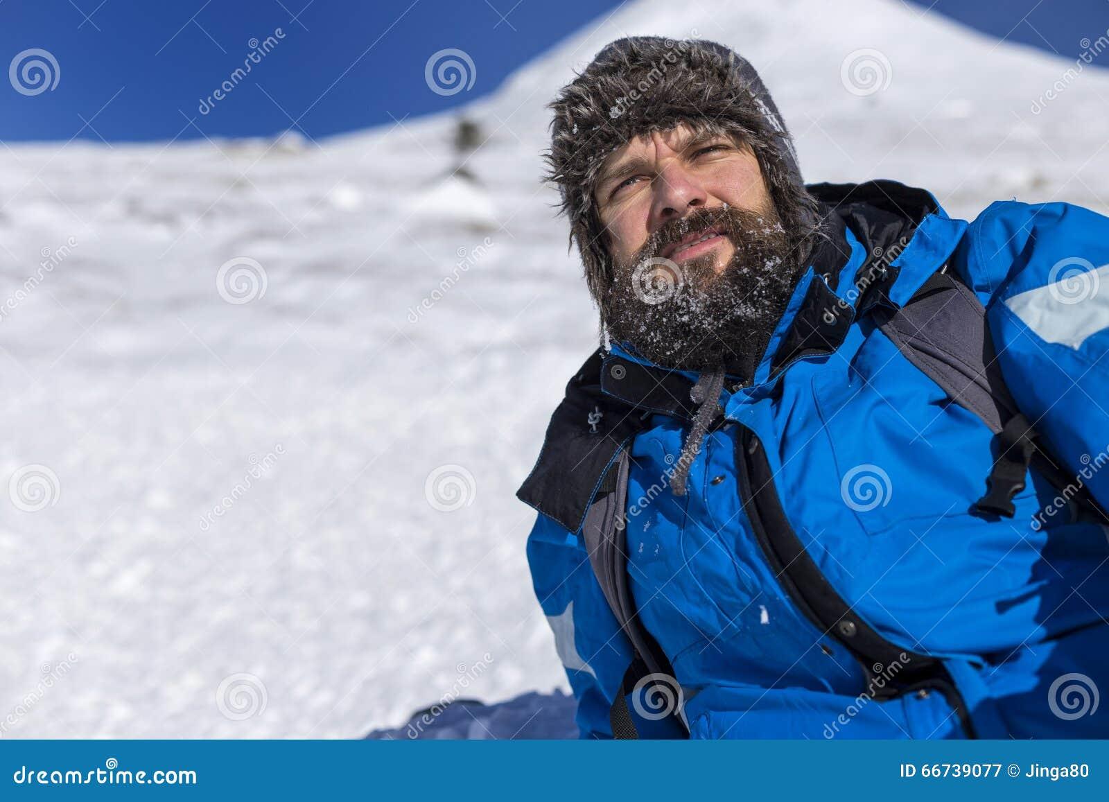 Skäggig trekker som vilar, medan klättra i vinter