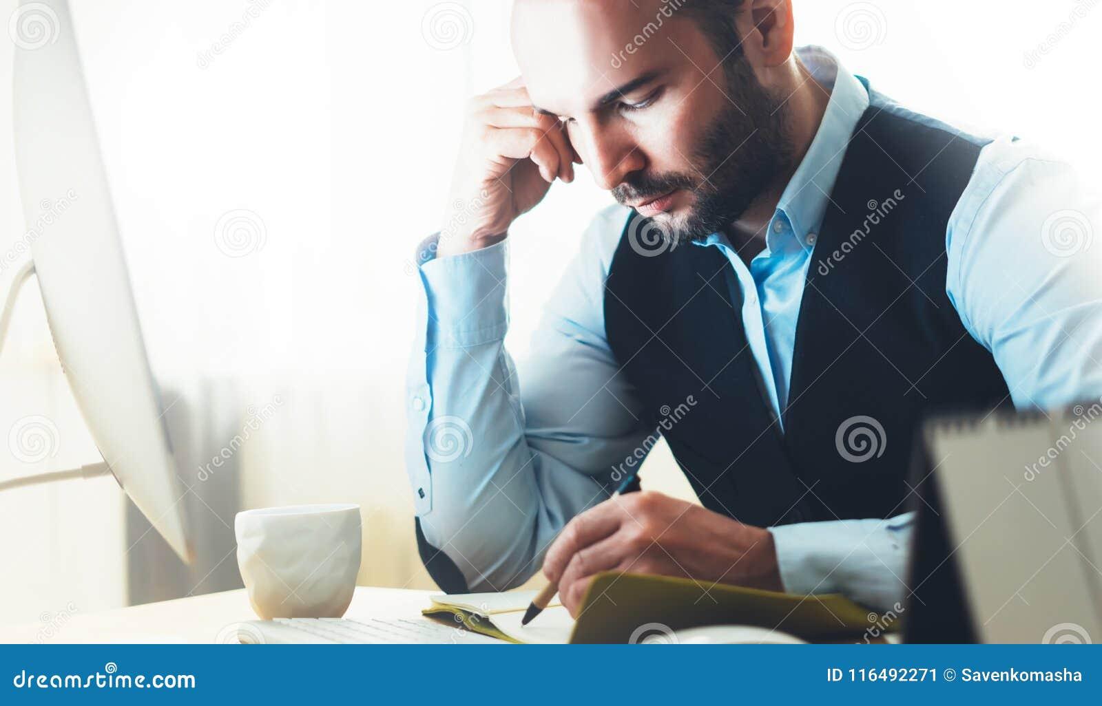 Skäggig ung affärsman som arbetar på modernt kontor Tänkande se för konsulentman i bildskärmdator Chefen skriver i noteboo