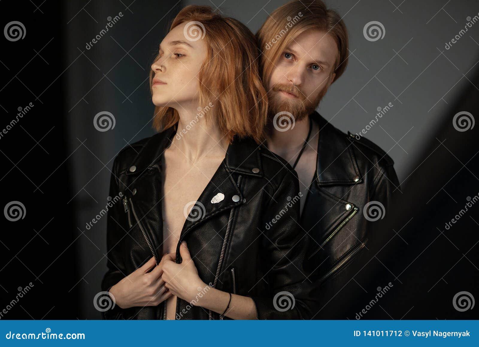 Skäggig ung man med långt brunt hår i stående behinde för läderomslag hans härliga flickvän