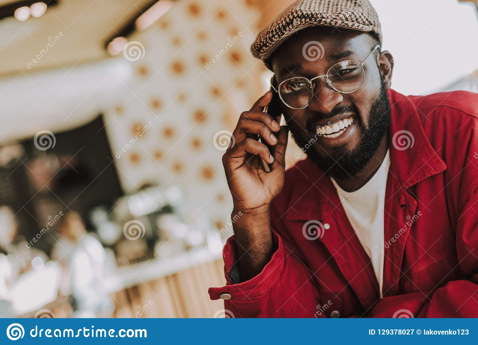 Skäggig ung man som talar på telefonen och glatt ler