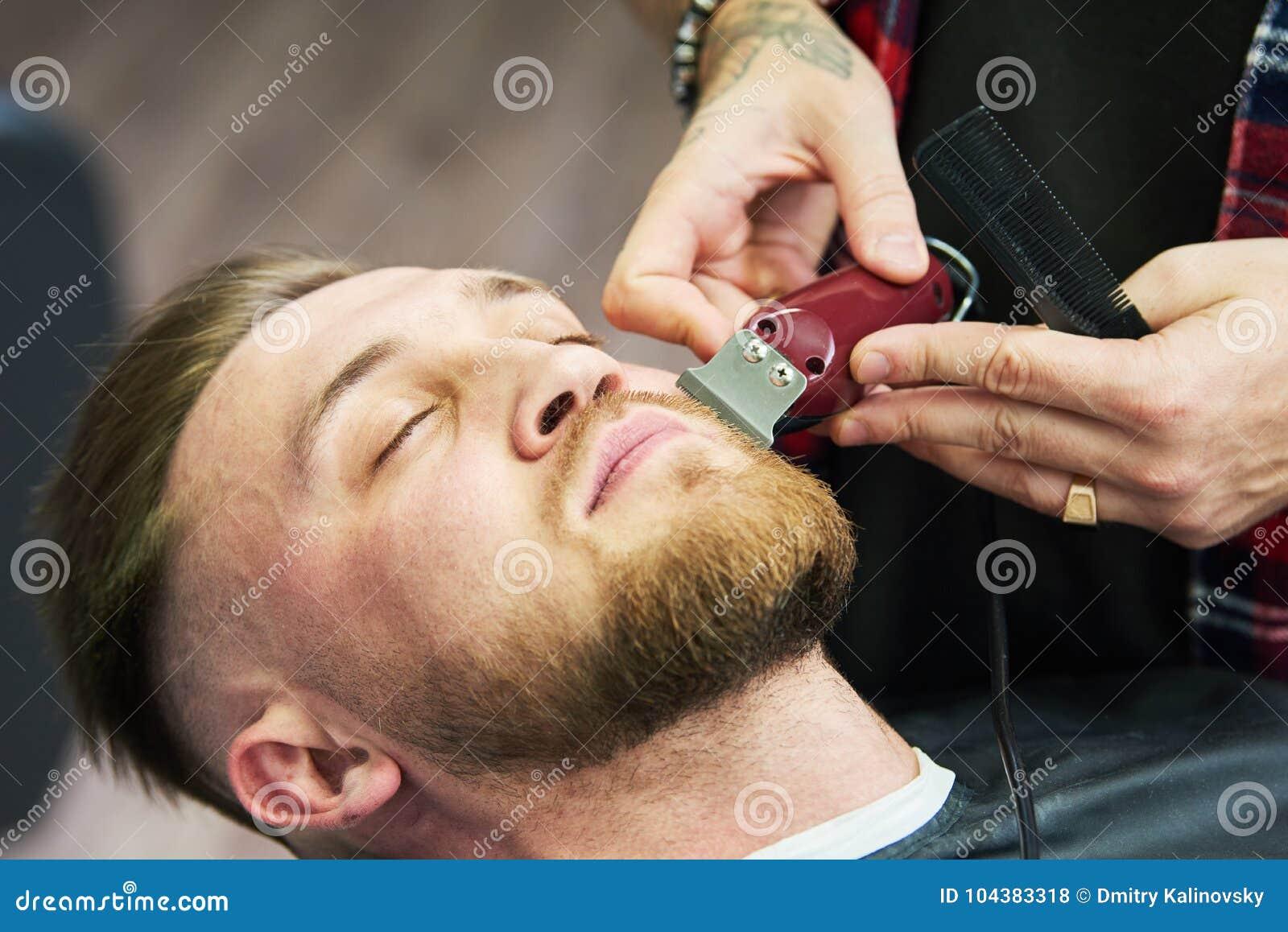 Skäggomsorg man, medan att klippa hans ansikts- hår klippte på frisersalongen