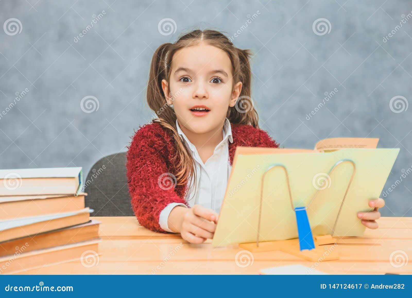 Skämtsam gullig liten flicka som har roligt, medan luta på tjocka böcker på den gråa bakgrunden Hennes h?r g?ras i fl?tor
