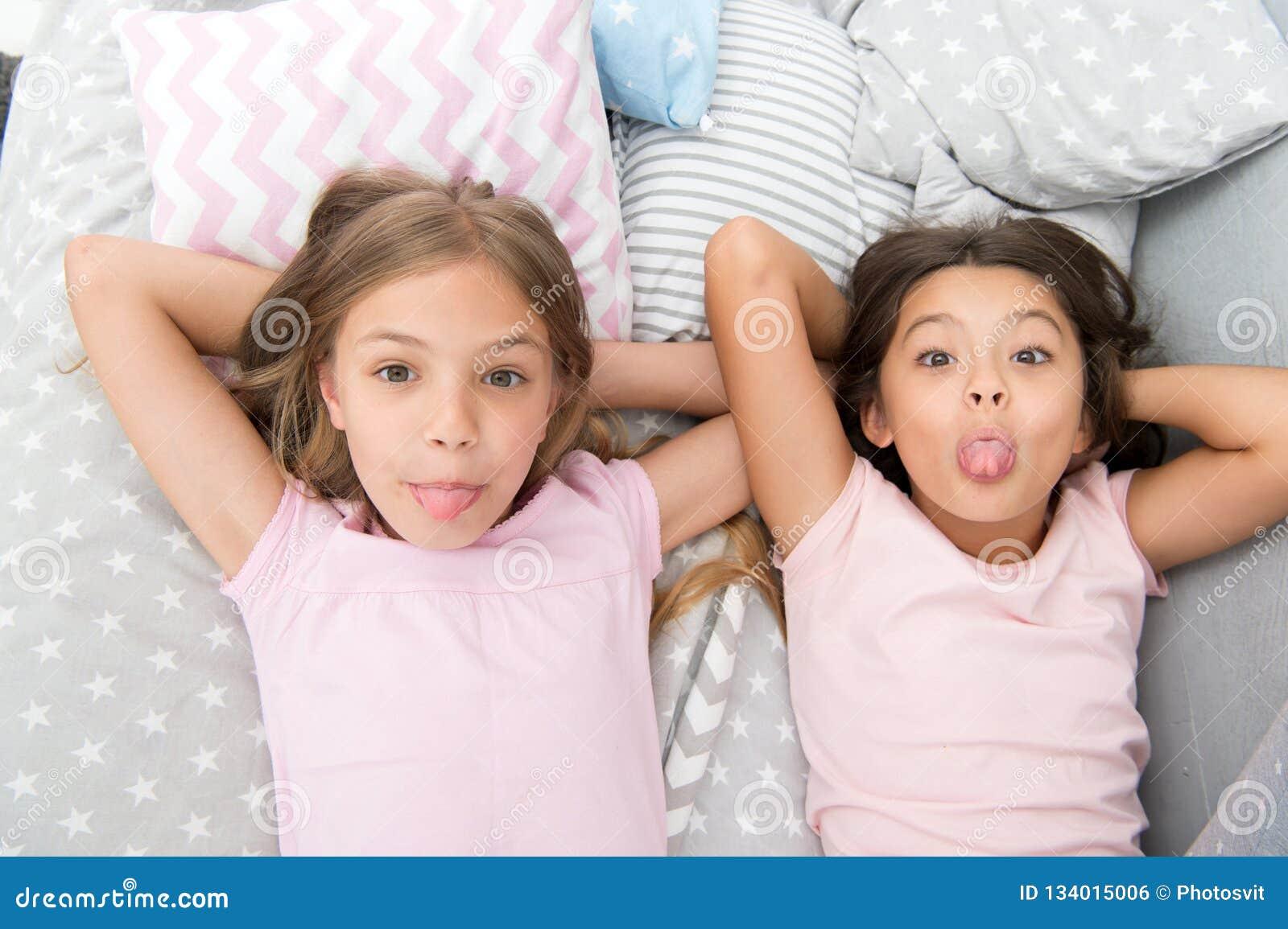 Skämtsamt gladlynt lynne för barn som har roligt tillsammans Pajamaparti och kamratskap Lyckliga små ungar för systrar som in kop