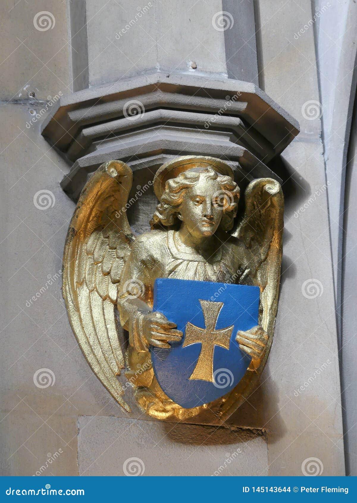 Sköld för innehav för skulptur för ängel för kyrkavägg guld- och se ner