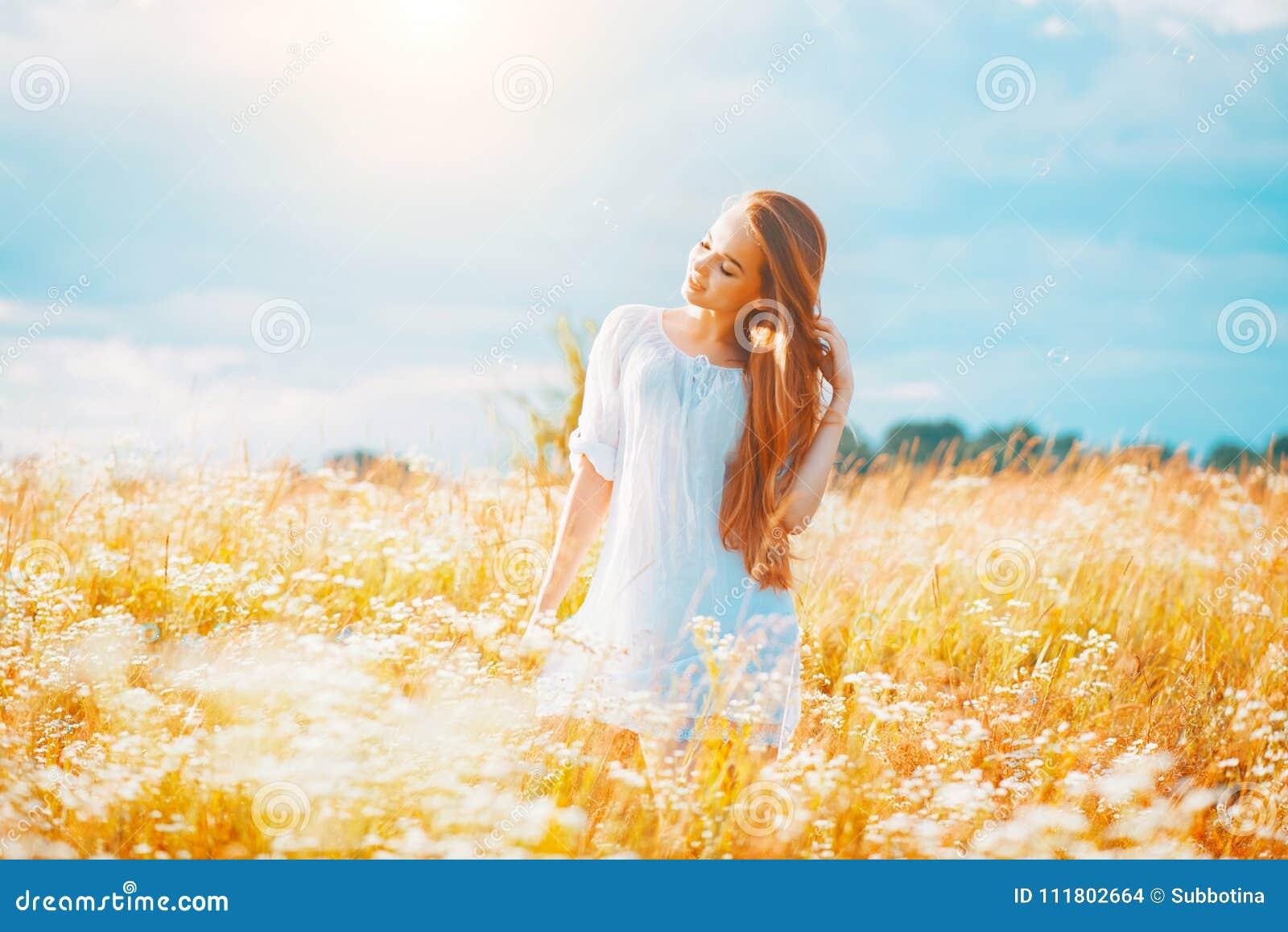 Skönhetflicka som tycker om utomhus naturen Härlig tonårs- modellflicka med sunt långt hår i den vita klänningen