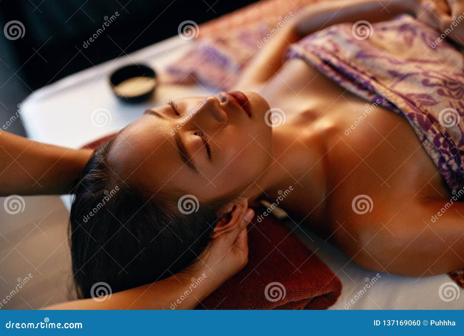 Skönhetkvinna som får ansikts- massage Händer som masserar kvinnahuvudet på den thailändska skönhetsalongen