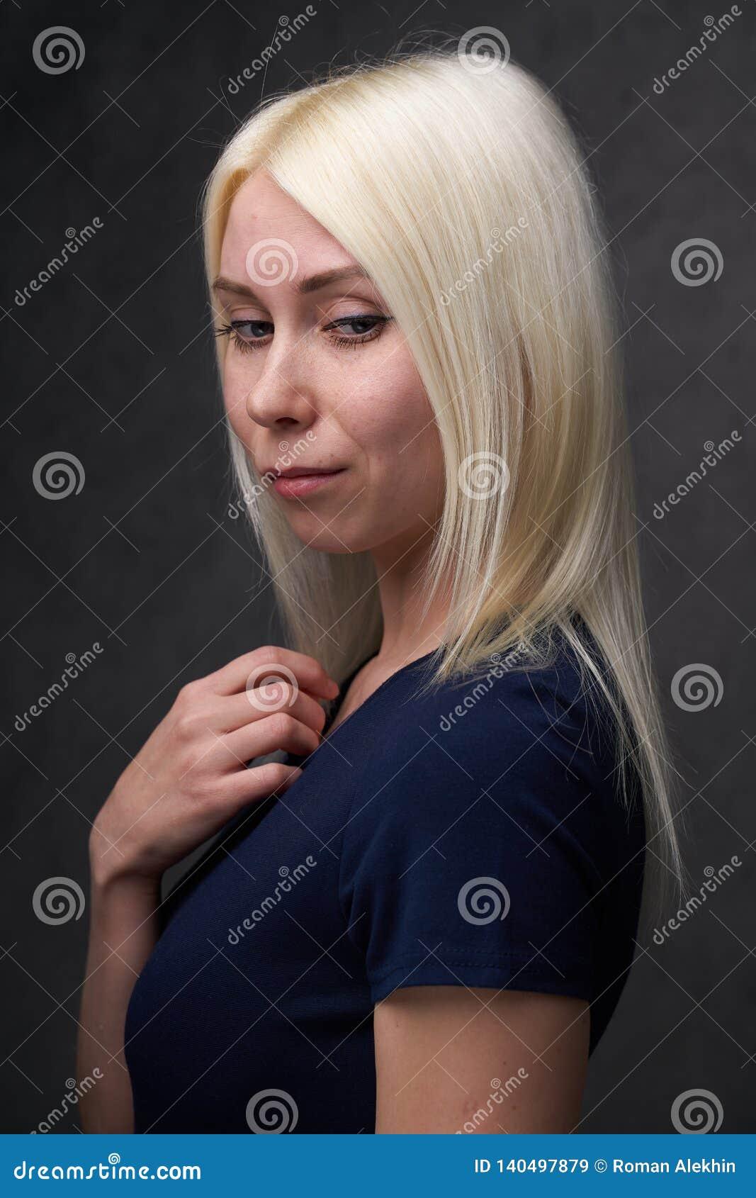 Skönhetkvinnlig som är blond i svart tillfällig kläder på grå bakgrund