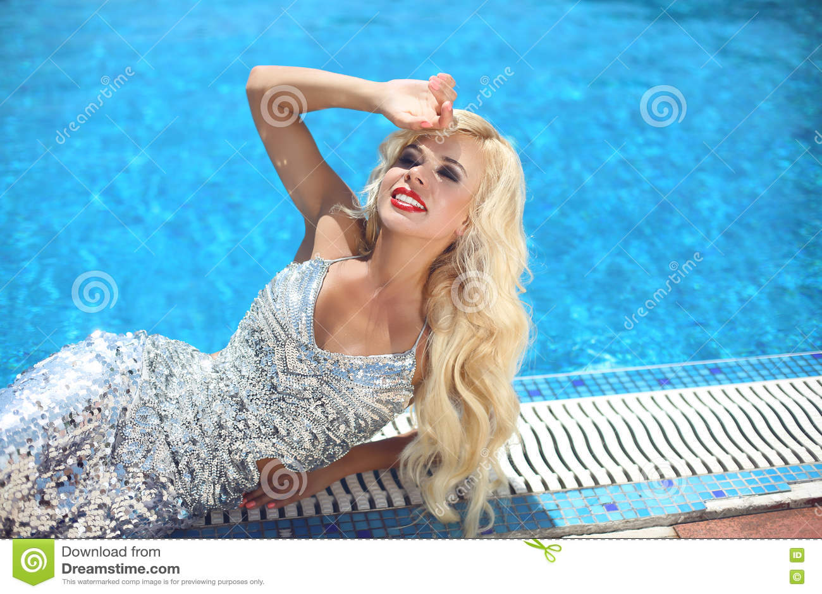 Skönhetmode som ler den blonda flickamodellen som poserar i partiklänningen ly