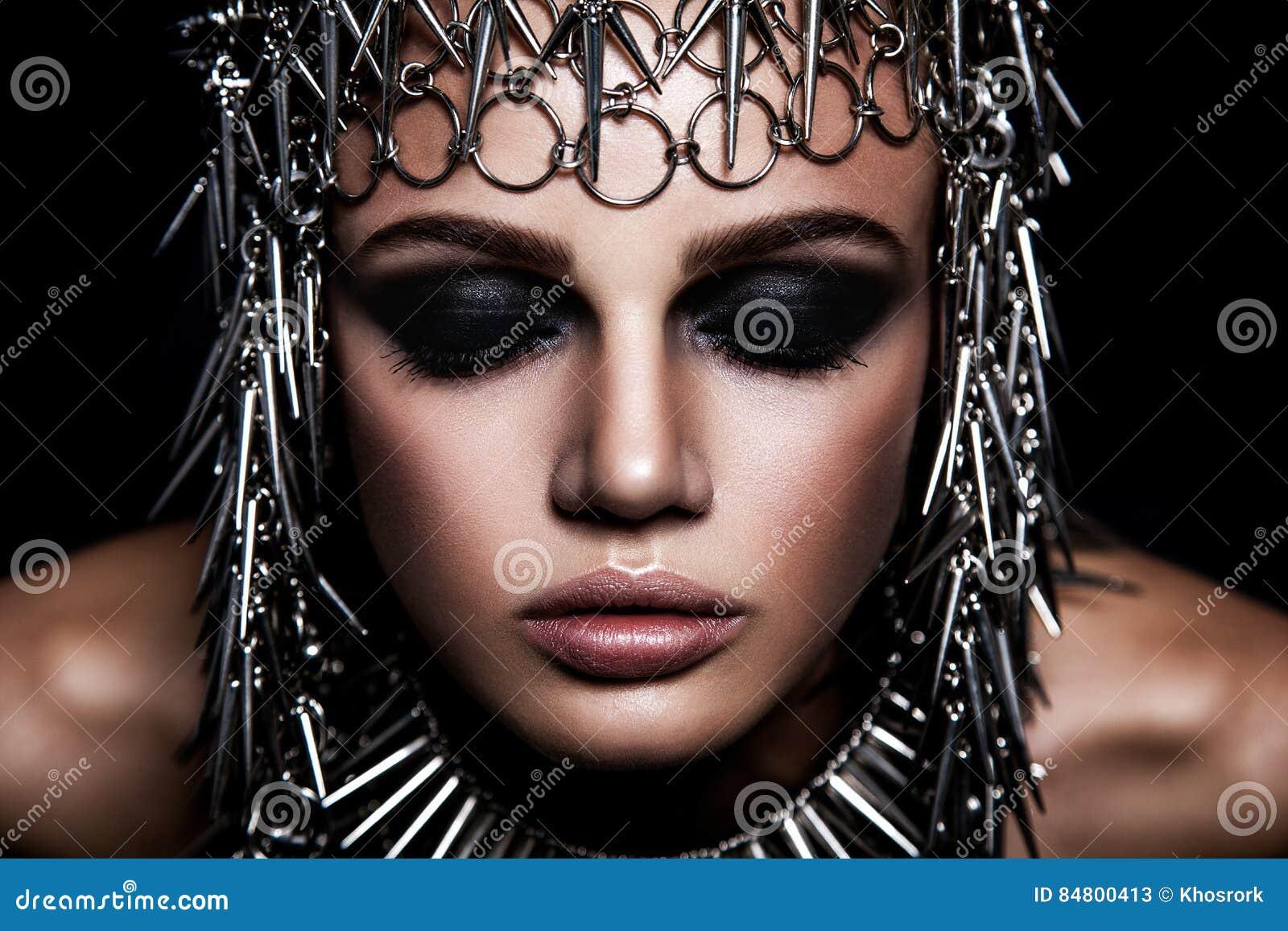Skönhetmodell för högt mode med metallisk headwear- och mörkermakeup och blåa ögon på svart bakgrund