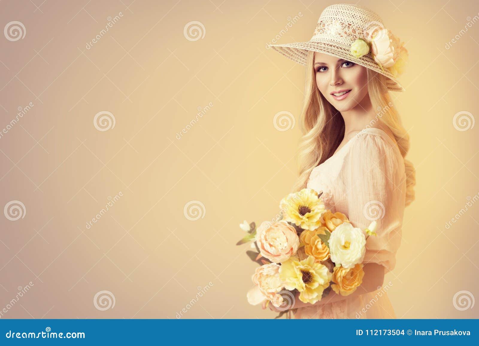 Skönhetmodell i bred brättehatt för mode, kvinna och pionblommor