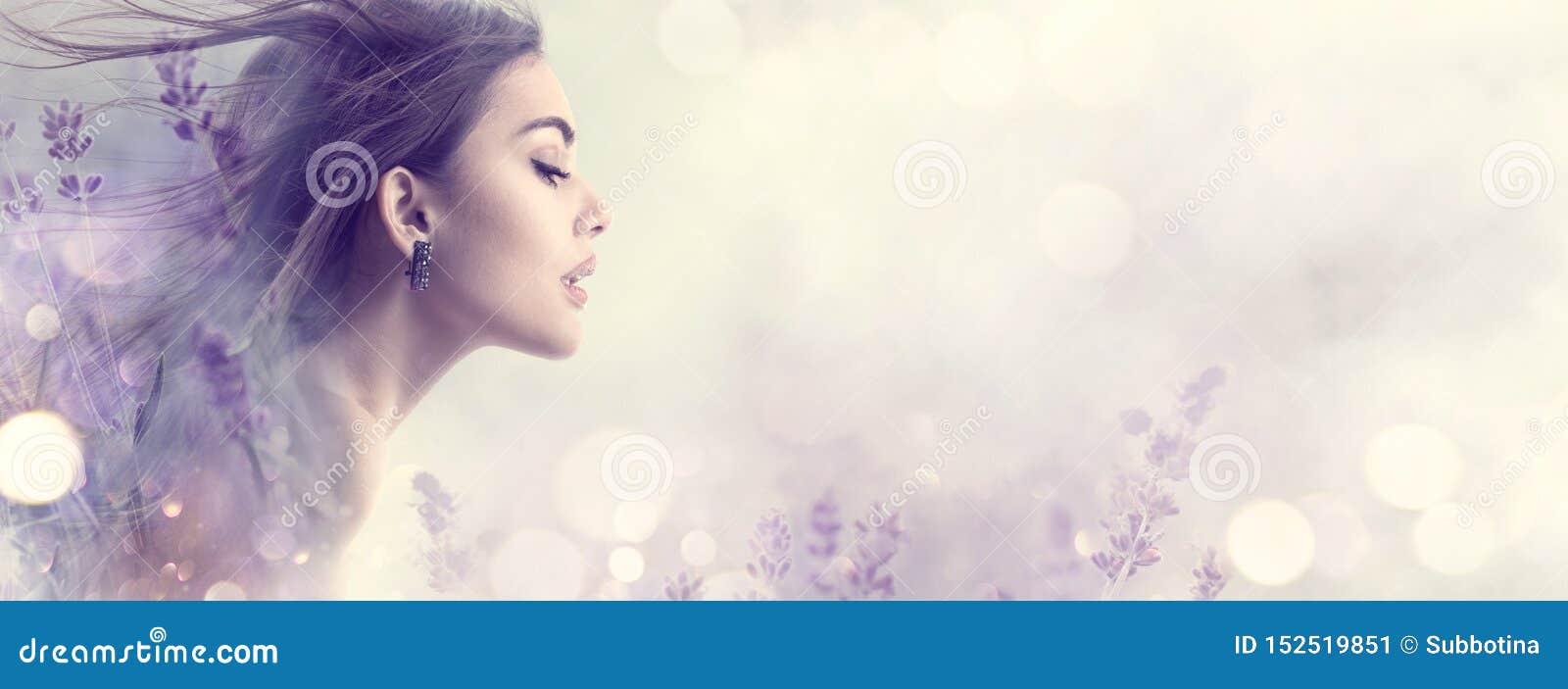 Skönhetmodellflicka med lavendelblommor Härlig ung brunettkvinna med för hårprofil för flyg den långa ståenden