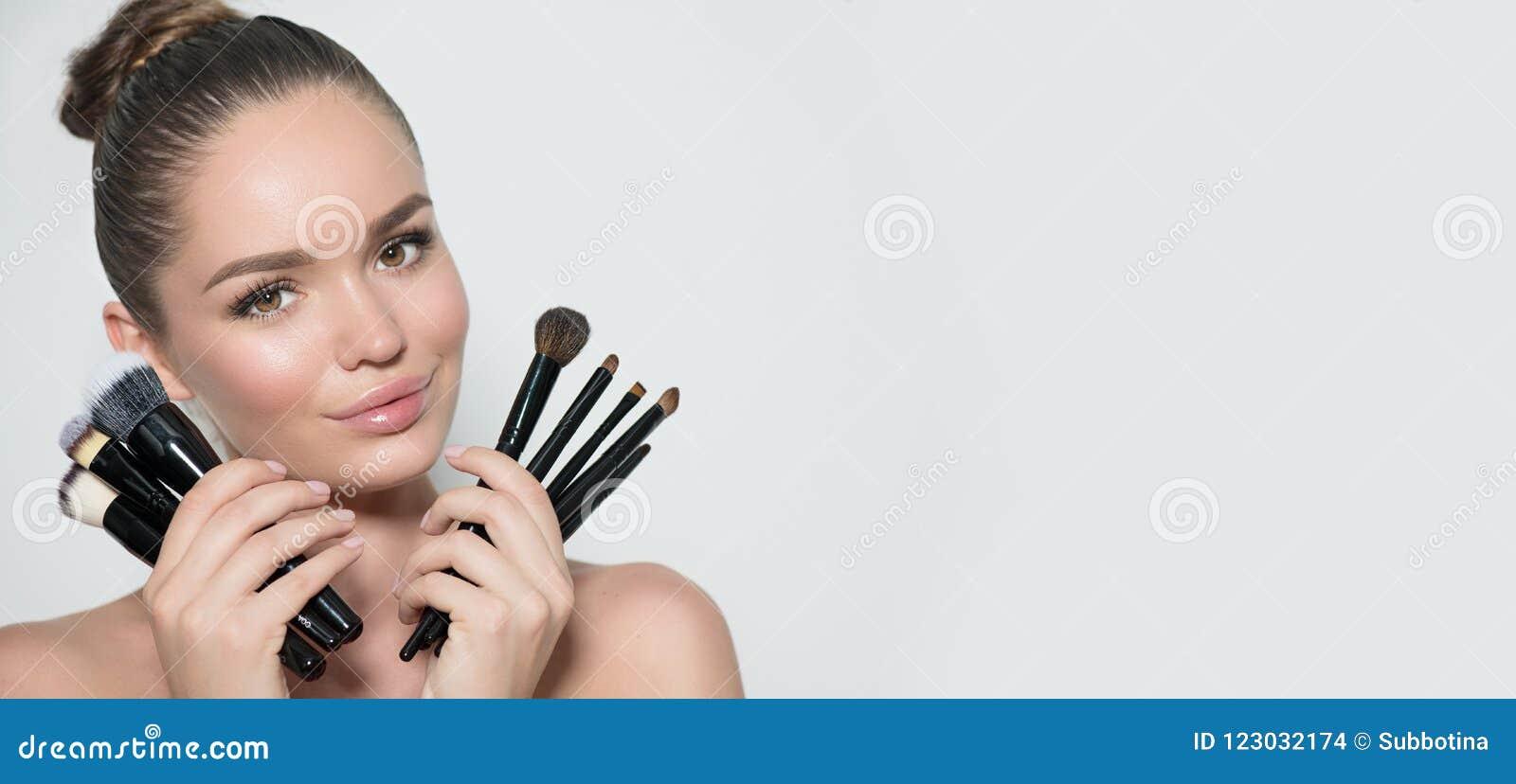 Skönhetmodellflicka, uppsättning för innehav för makeupkonstnär av sminkborstar och le Ung kvinna för härlig brunett med perfekt