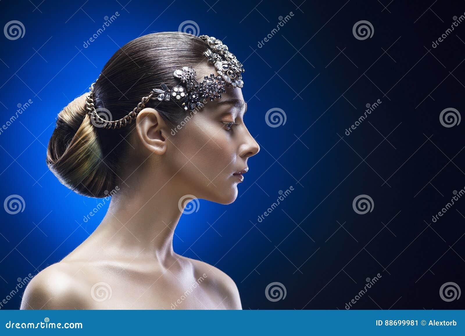 Skönhetsidostående av den unga kvinnan med en exakt frisyr och prydnaden i hår på en blå lutningbakgrund