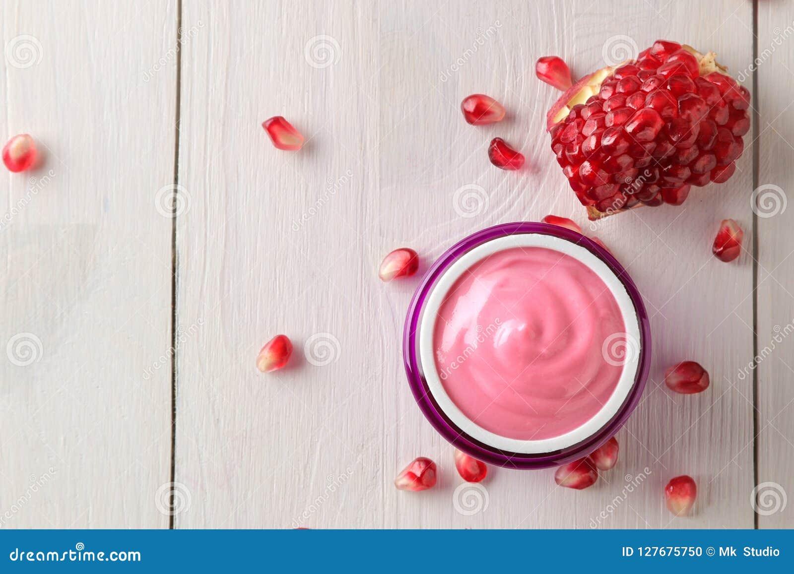Skönhetsmedelkräm i en lila krus och med den nya granatäpplet på en vit trätabell Granatäppleextrakt Skönhetsmedel