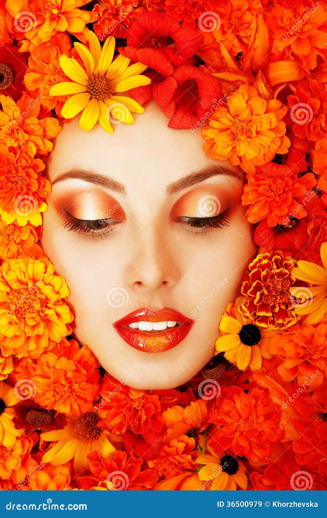 Skönhetstående av den härliga kvinnliga framsidan med orange blommor