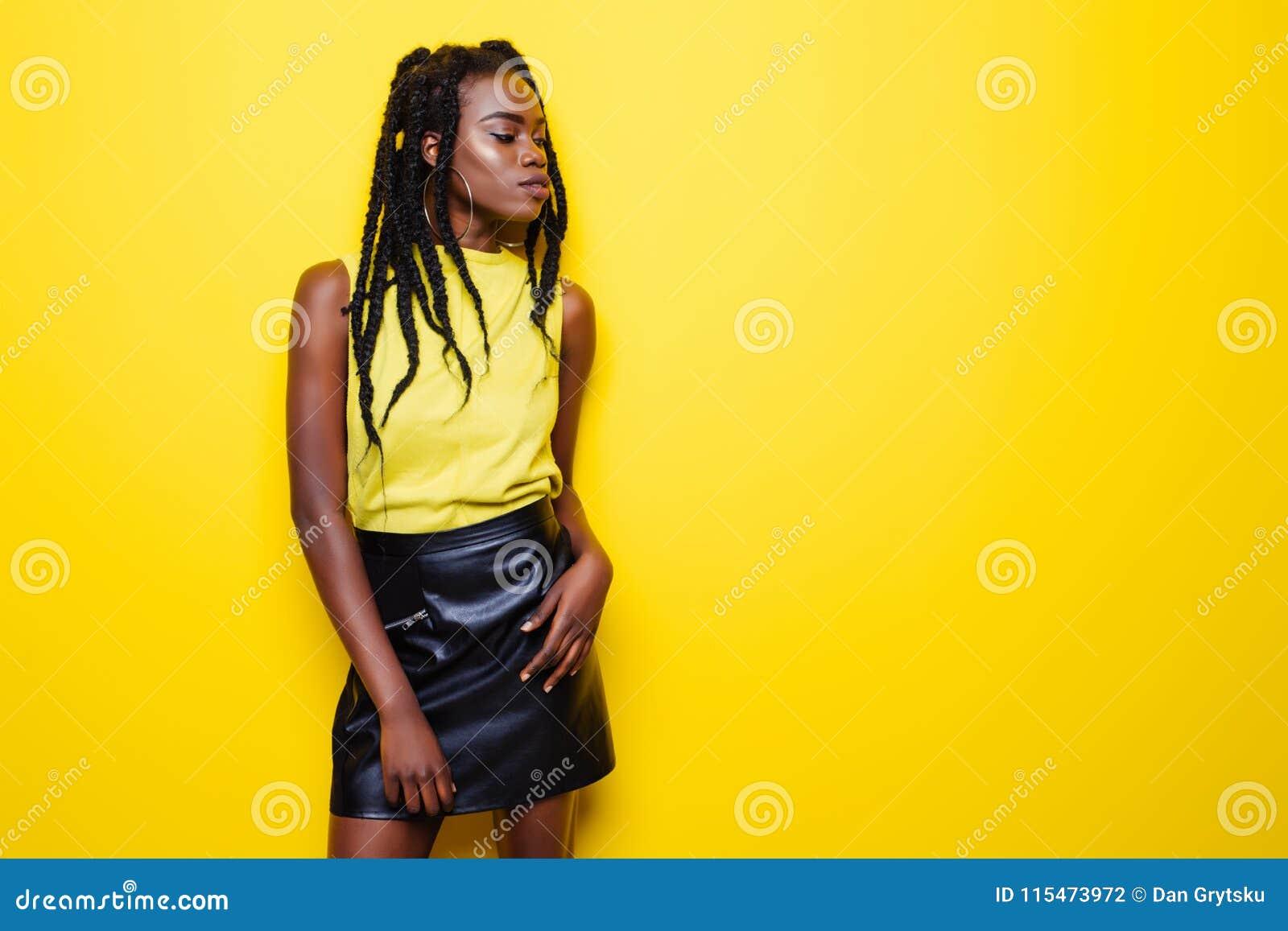 Skönhetstående av den unga afrikansk amerikanflickan med den afro frisyren Flicka som poserar på gul bakgrund och att se kameran