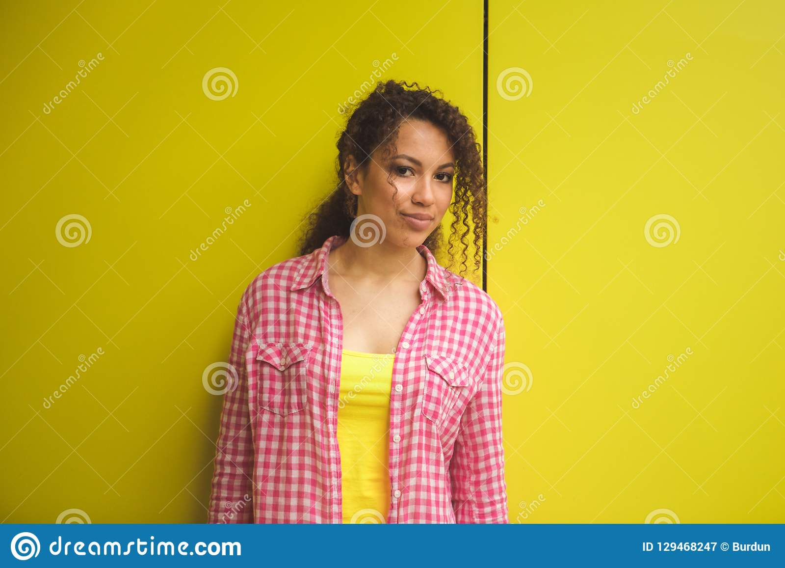 Skönhetstående av den unga afrikansk amerikanflickan med den afro frisyren Flicka som poserar på gul bakgrund som ser kameran