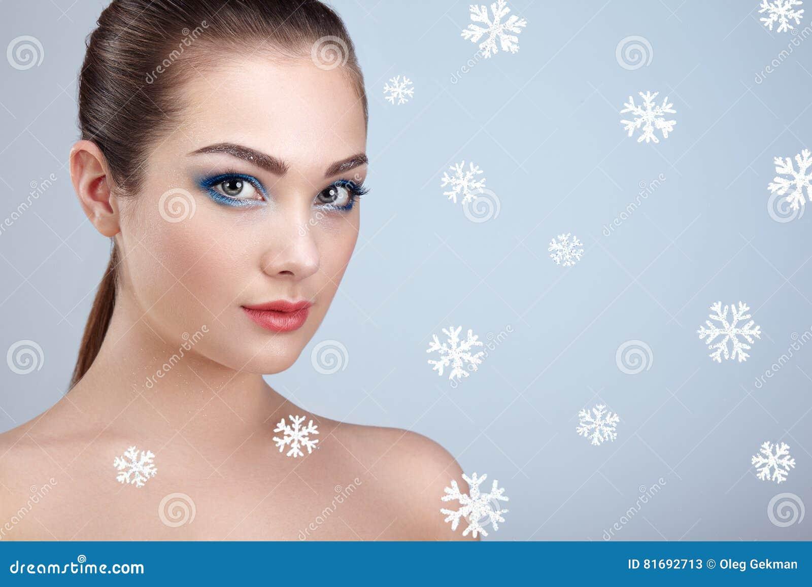 Skönhetstående av den unga härliga kvinnan över snöig